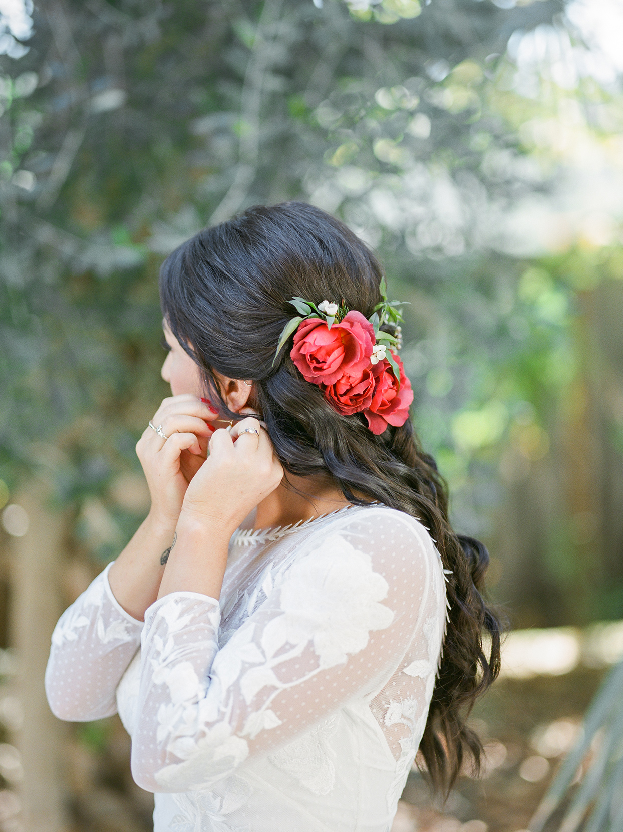 bride adjusting earrings with long wavy hair and red flower