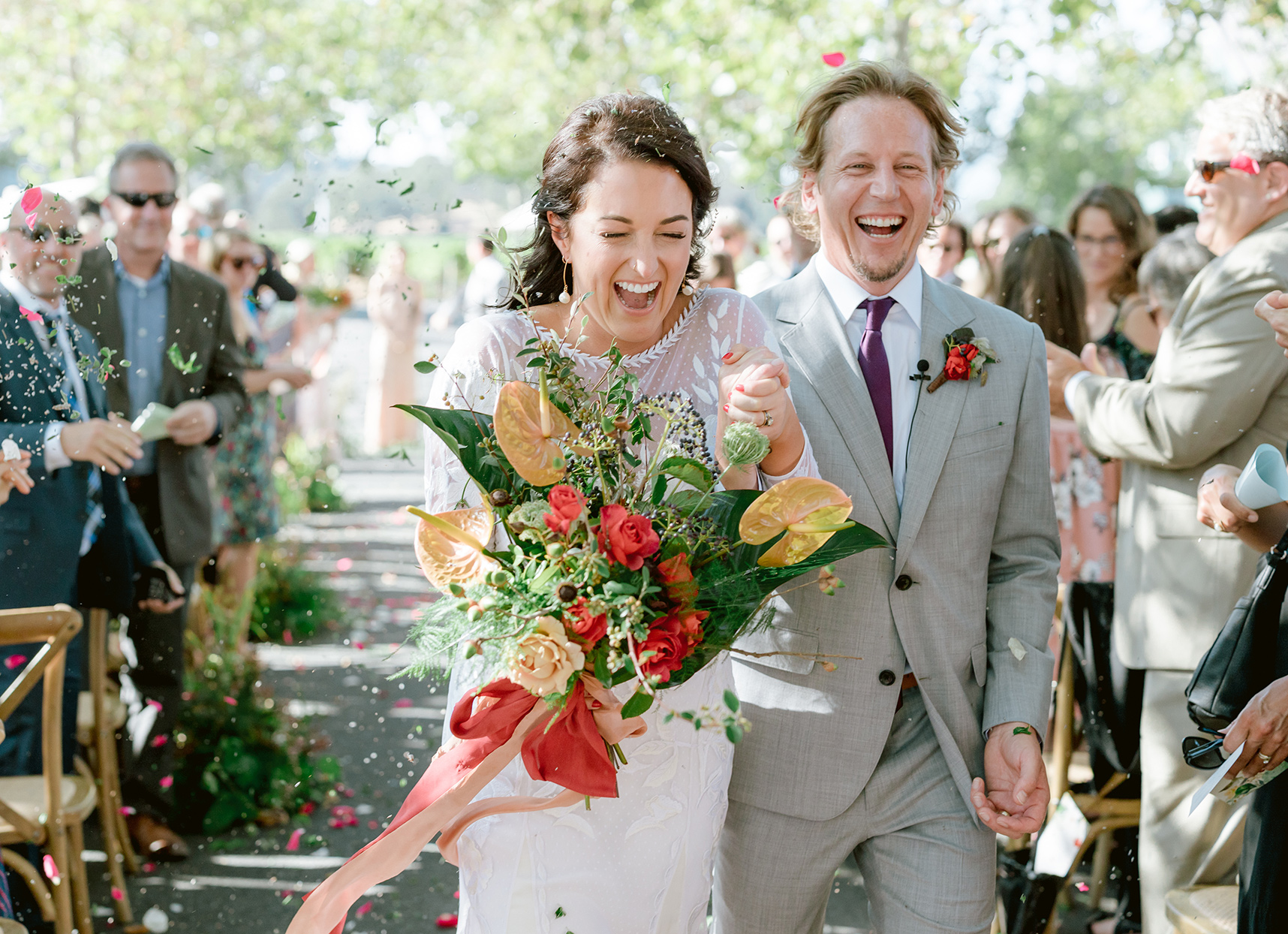 wedding couple holding hands as they leave ceremony showered in petals