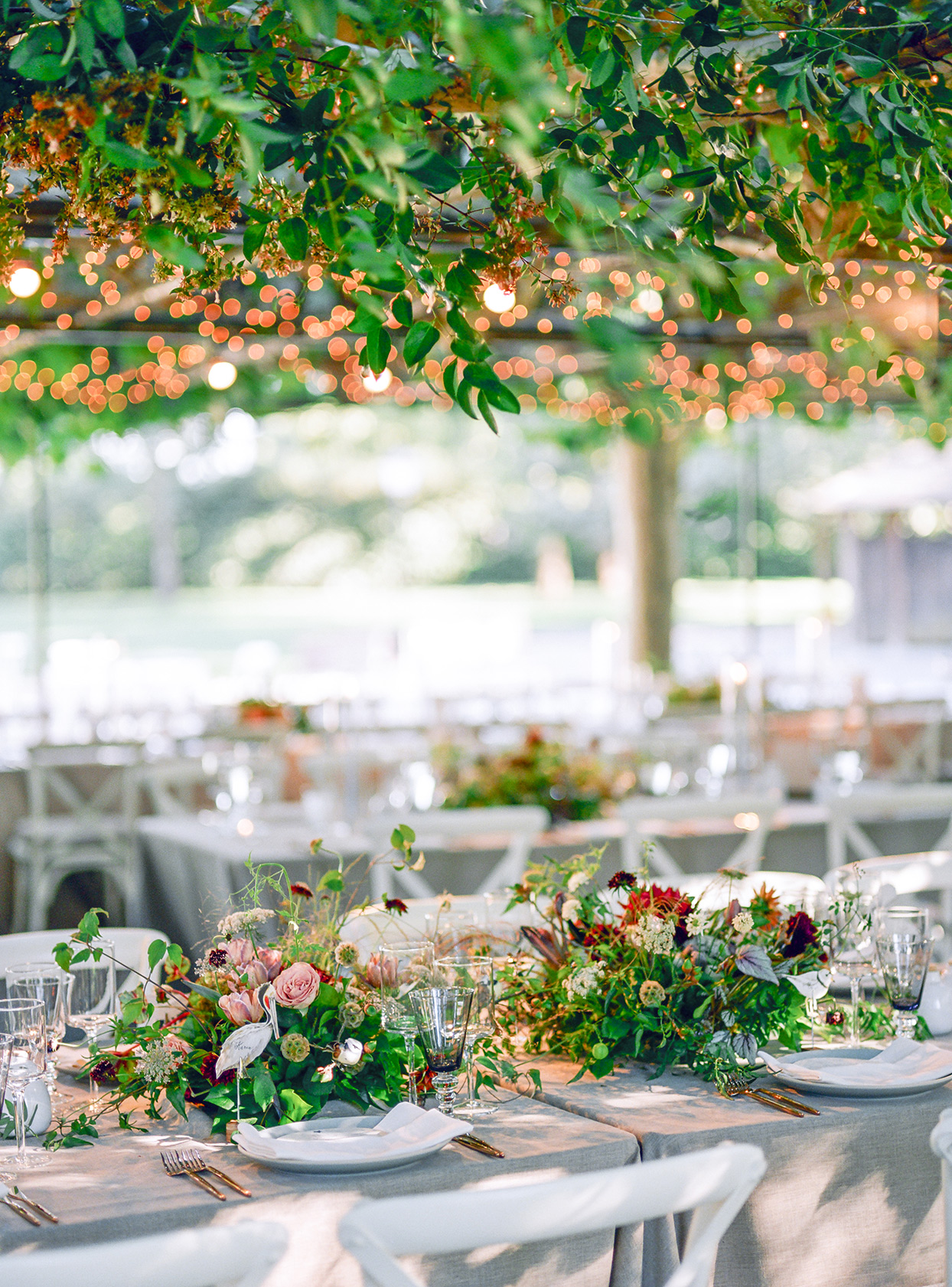 long elegant tables with fall centerpieces and hanging florals at outdoor reception