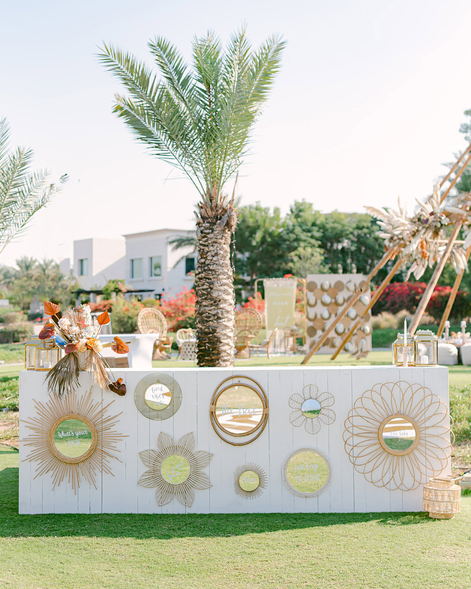 white outdoor bar decorated with floral mirrors