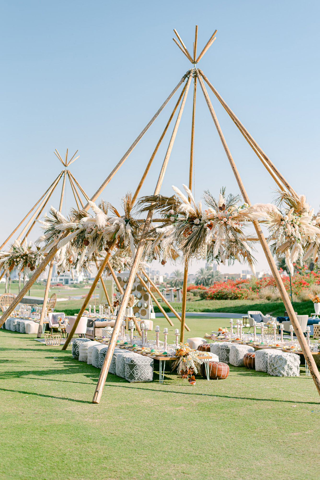 reception tables under large teepee structures