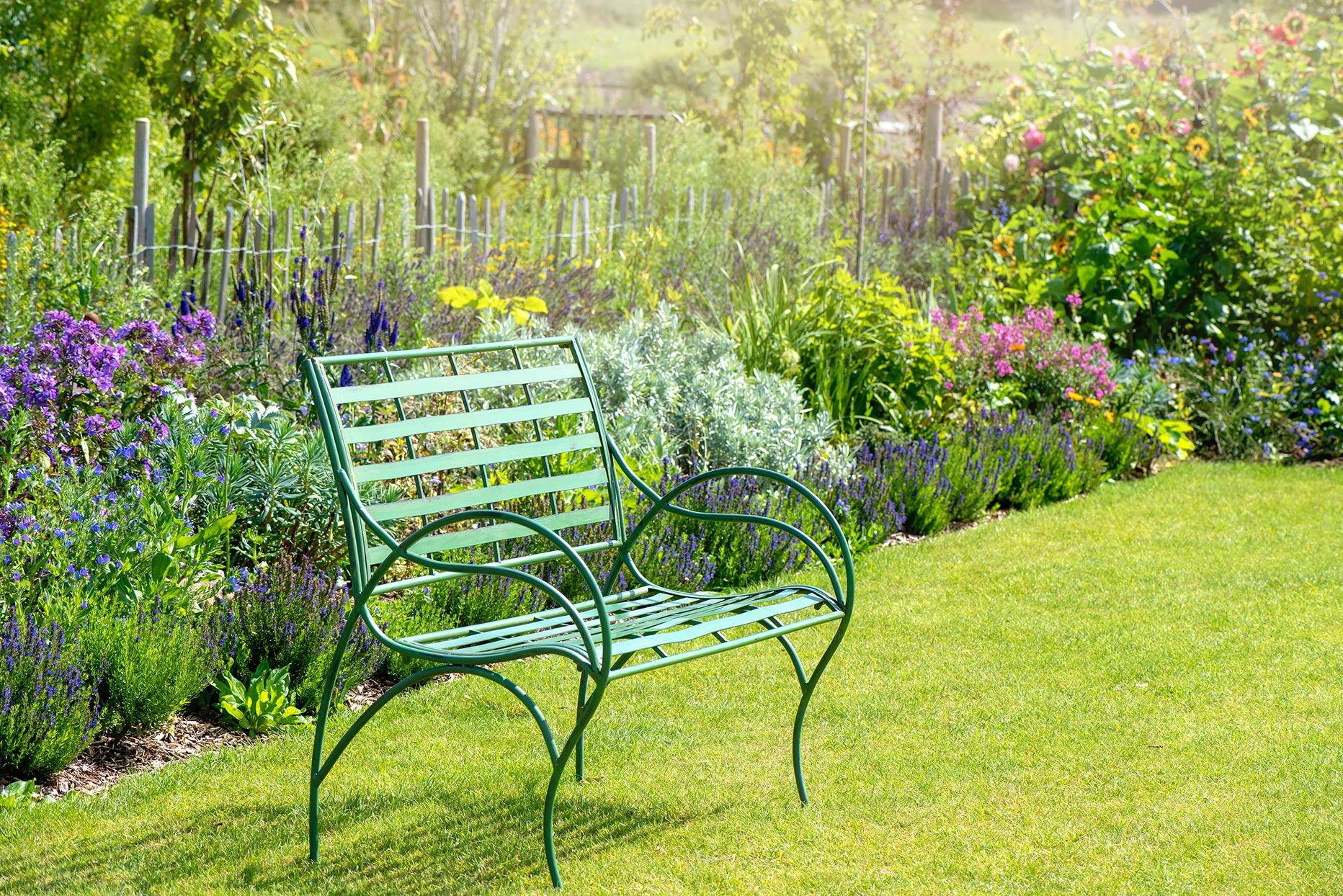 green metal bench in garden