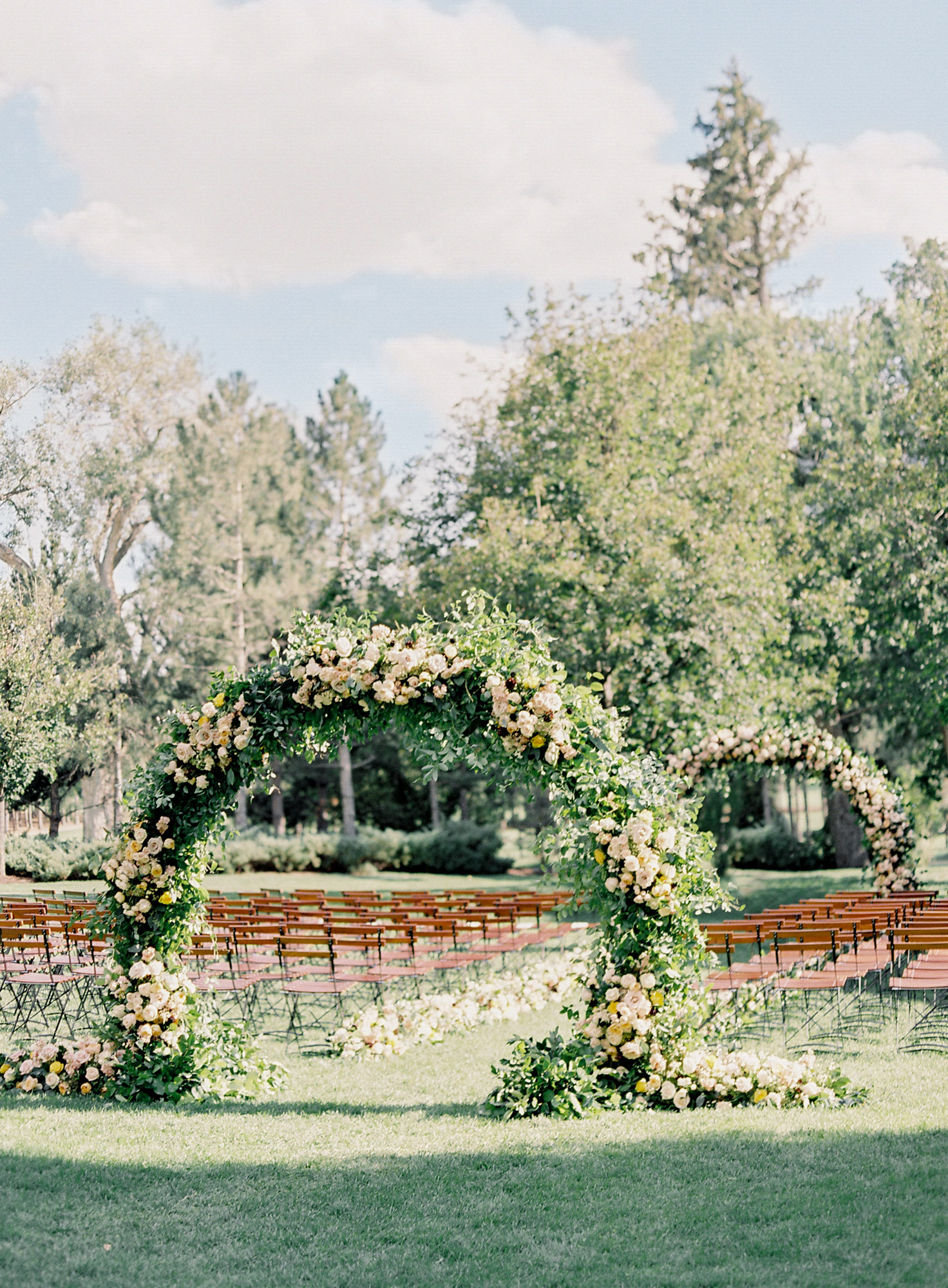 outdoor wedding ceremony space with floral arches