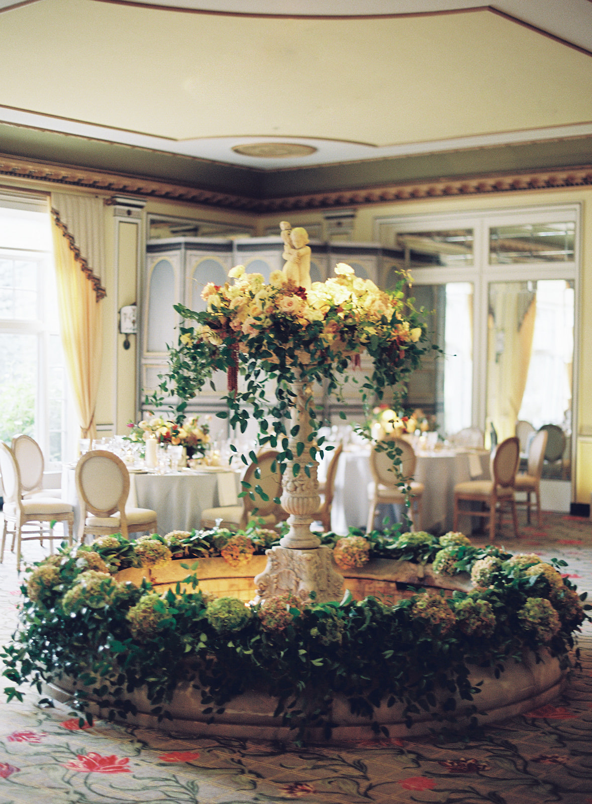 indoor fountain surrounded by round tables with centerpieces