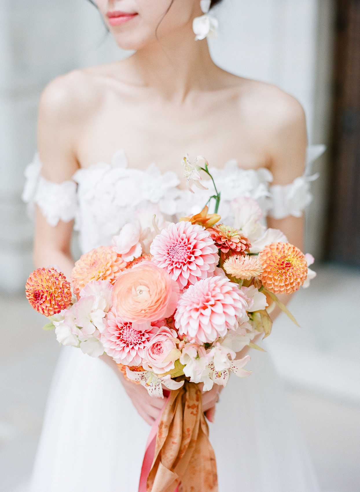 pastel pink and orange floral bouquet in bride's hands