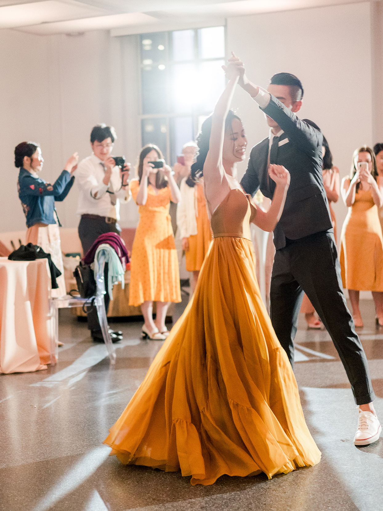 bride in yellow and groom twirling for wedding first dance