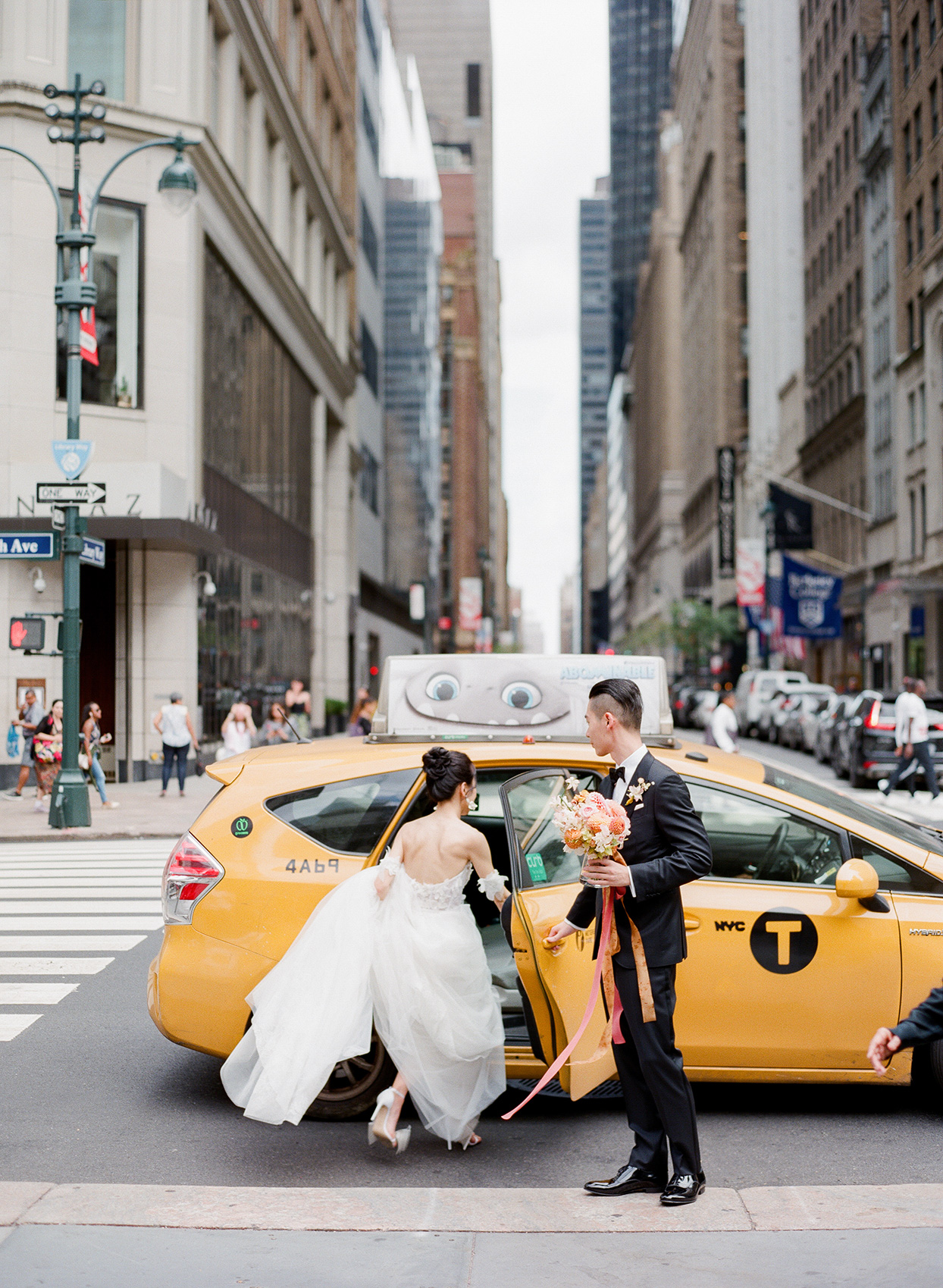 bride and groom getting in yellow taxi in manhattan
