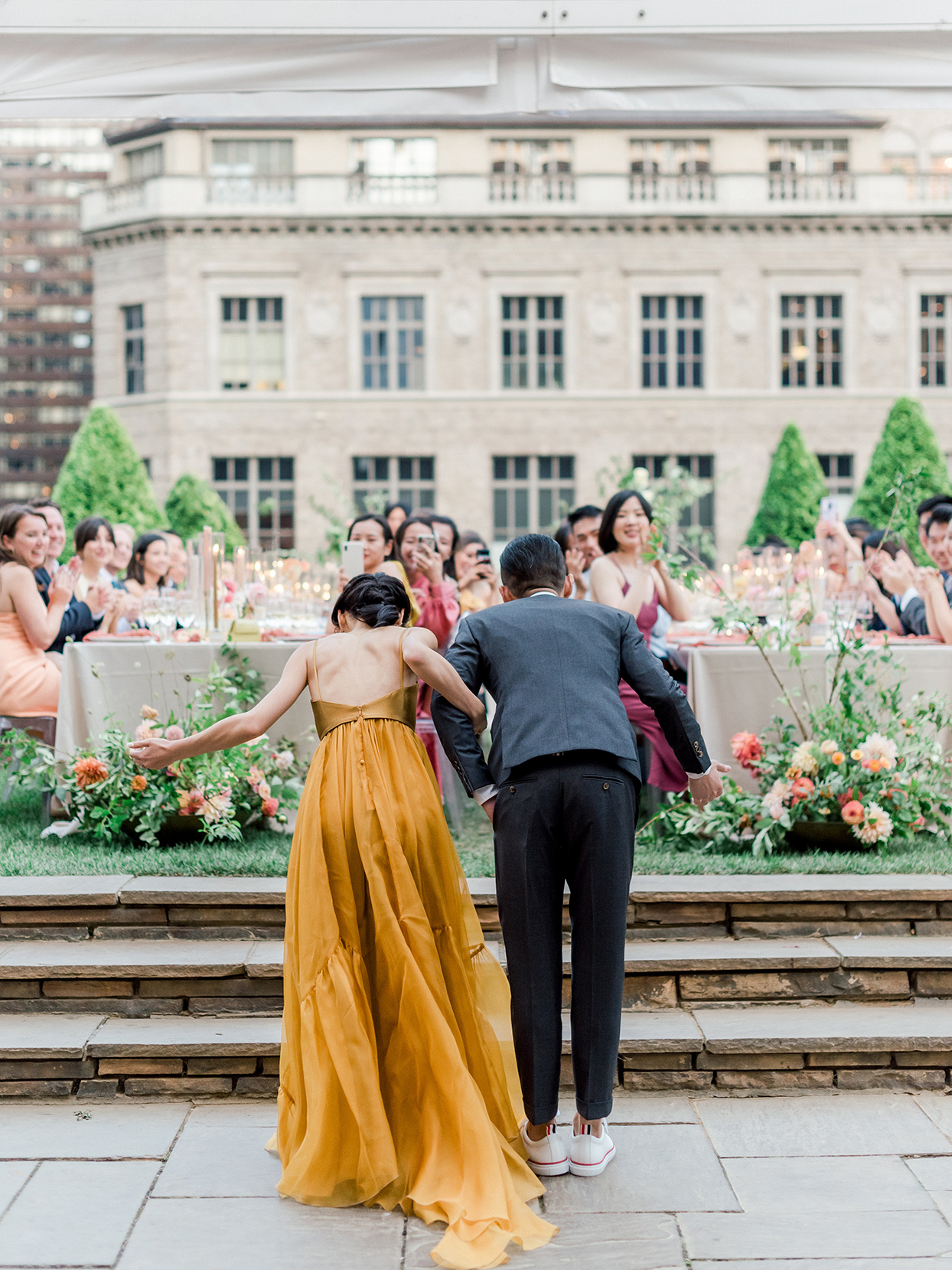 bride and groom bowing to guests in different reception outfits