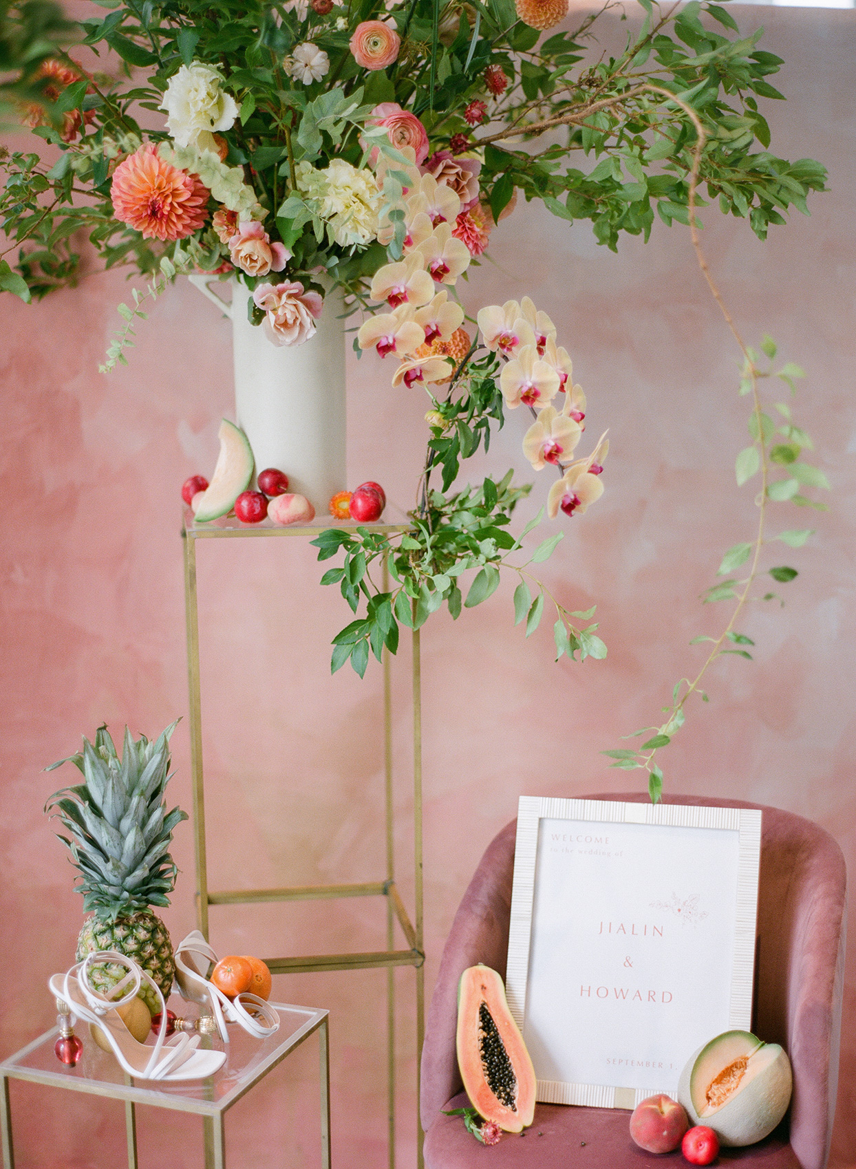 wedding welcome sign on blush chair with floral and fruit wedding decor