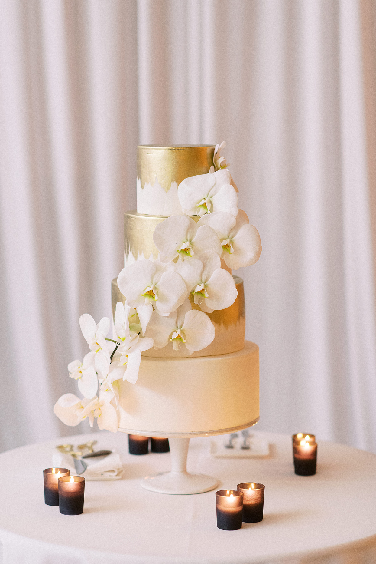 Wedding cake with three gold-topped layers on top of a tier iced in white