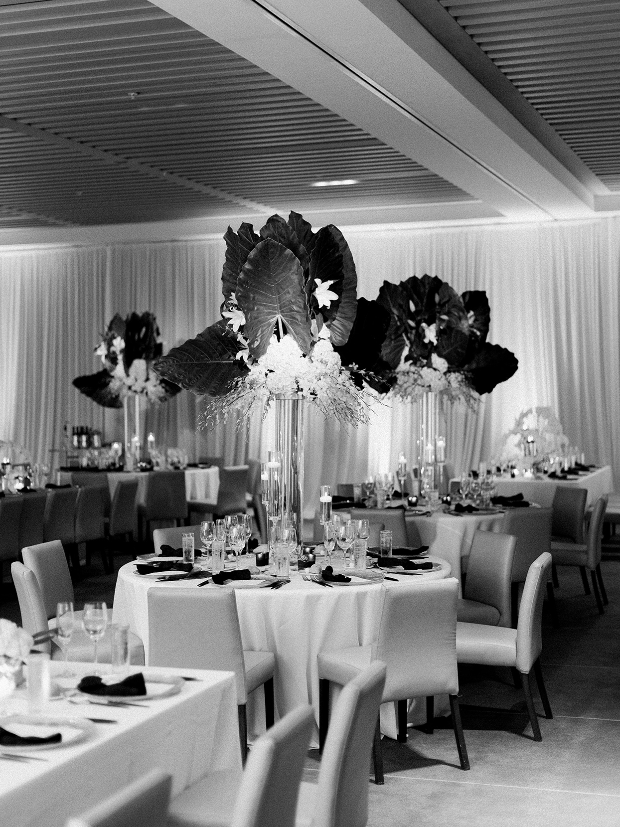 Wedding reception with mix of round and rectangle tables with assorted greenery and florals