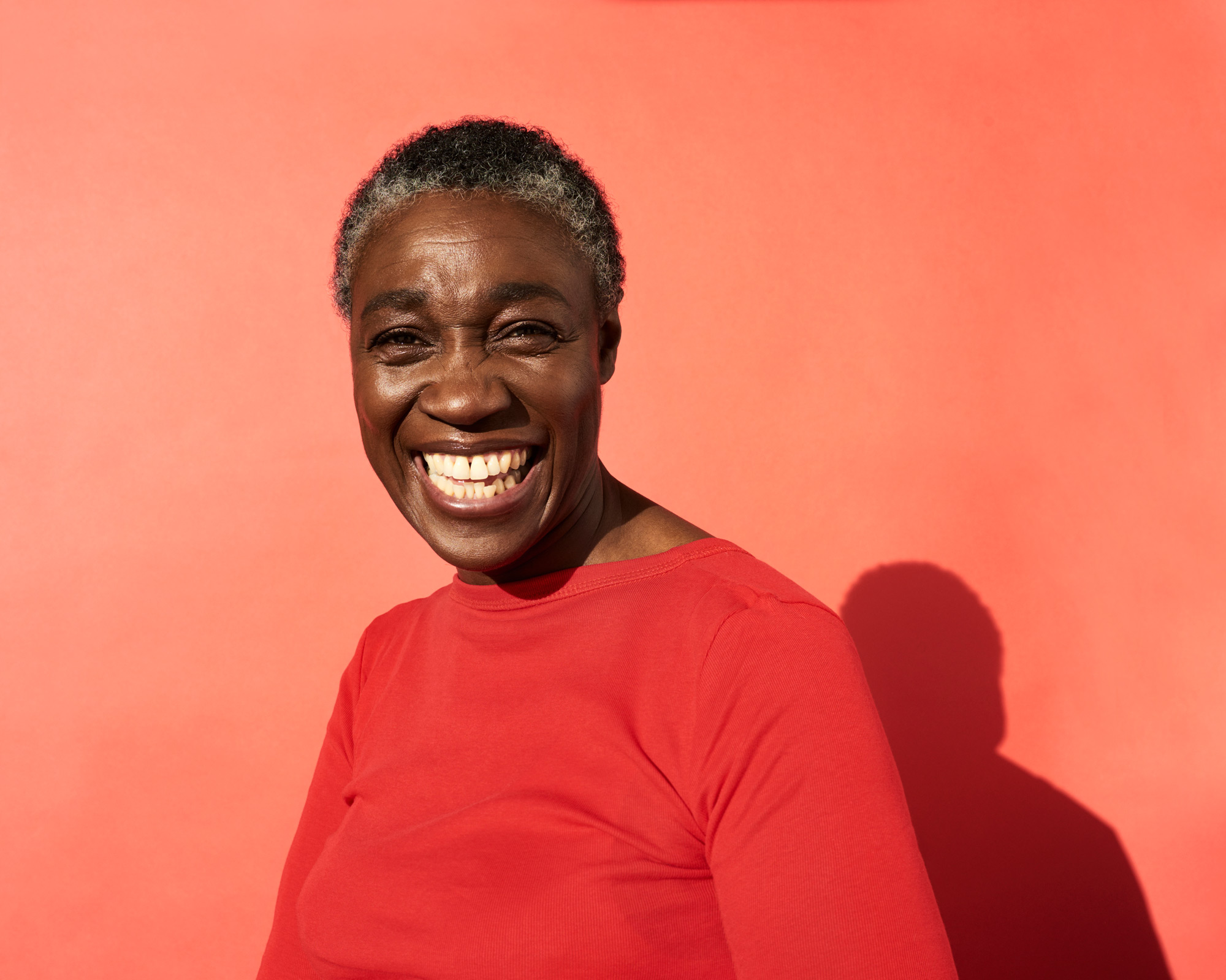 African American woman in red shirt smiling