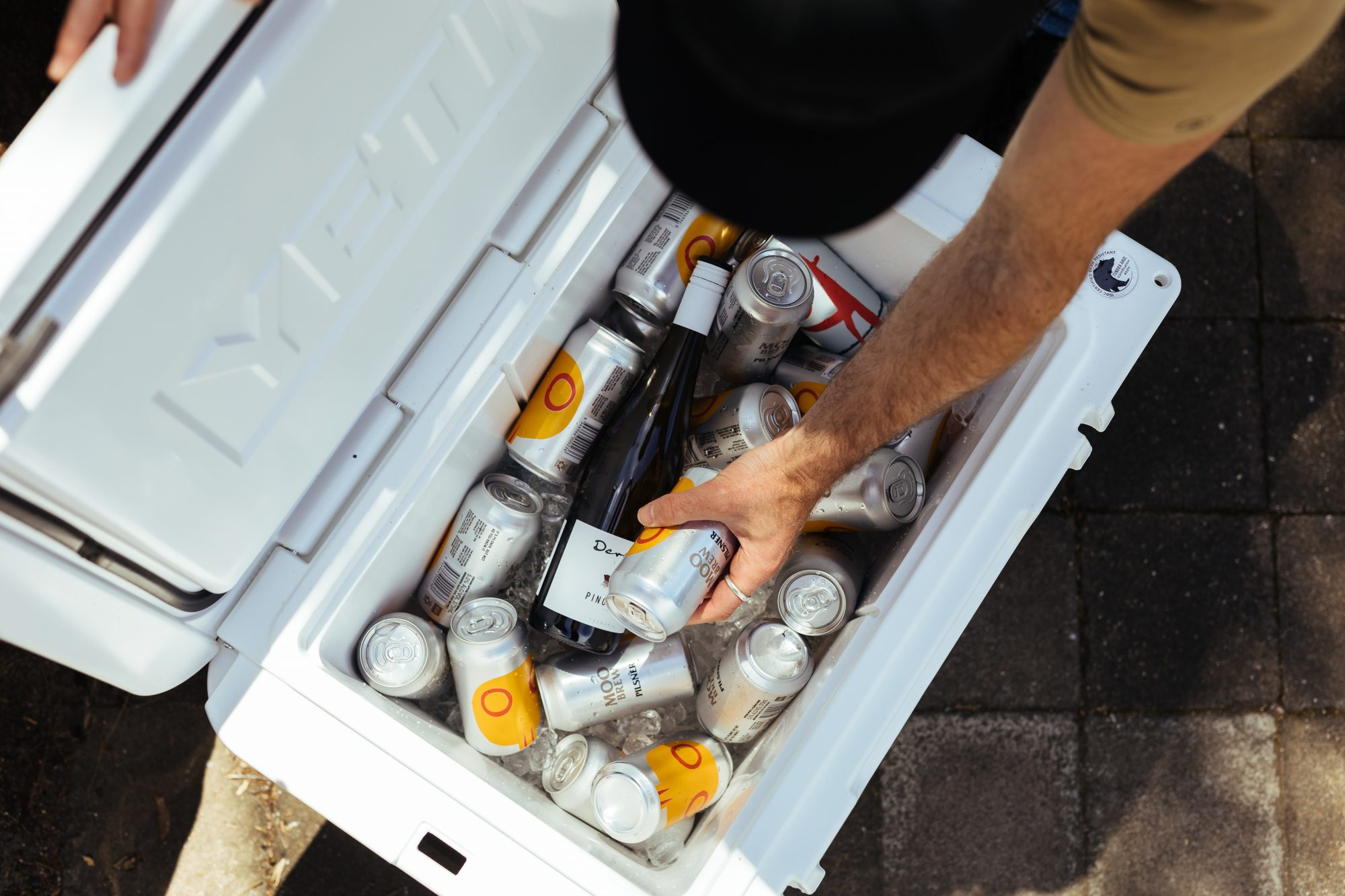 Man reaching into cooler packed with drinks
