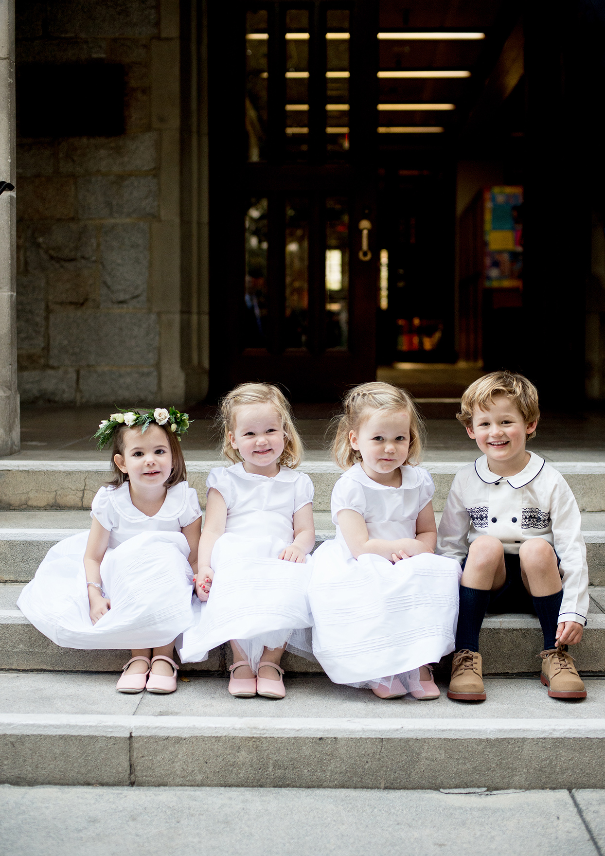 wedding kids dressed in white sitting on church steps