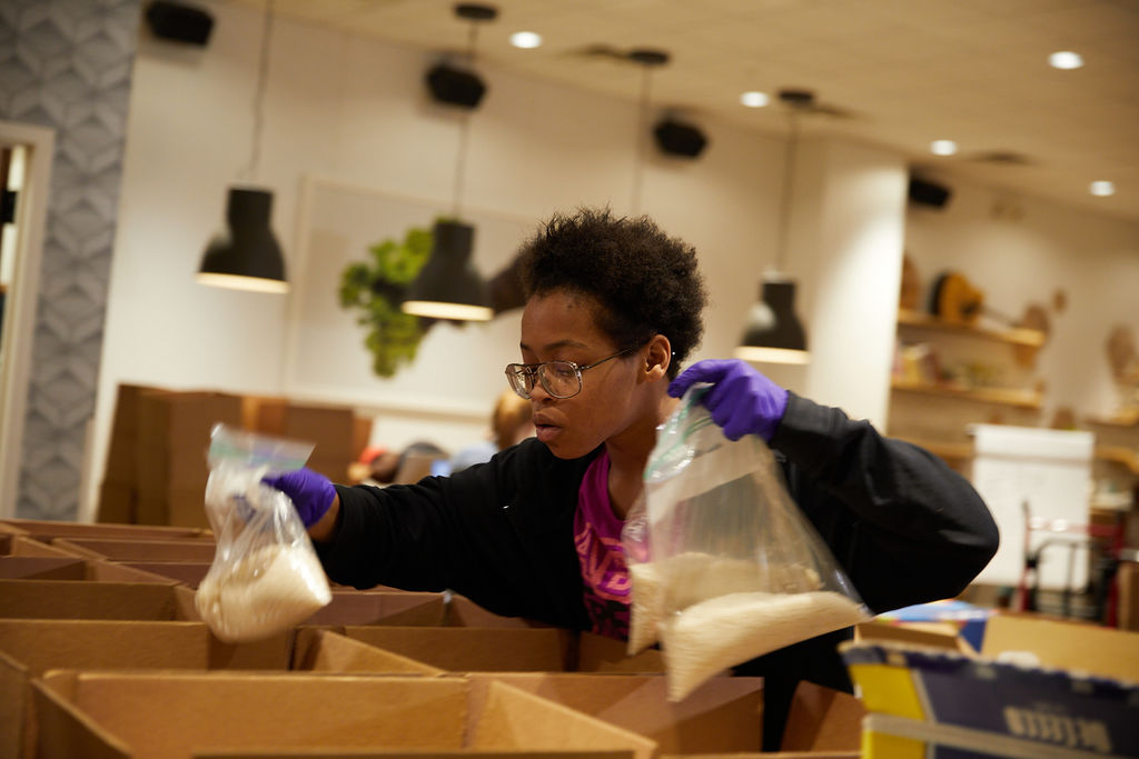 employee packing boxes to send meals to families during COVID-19