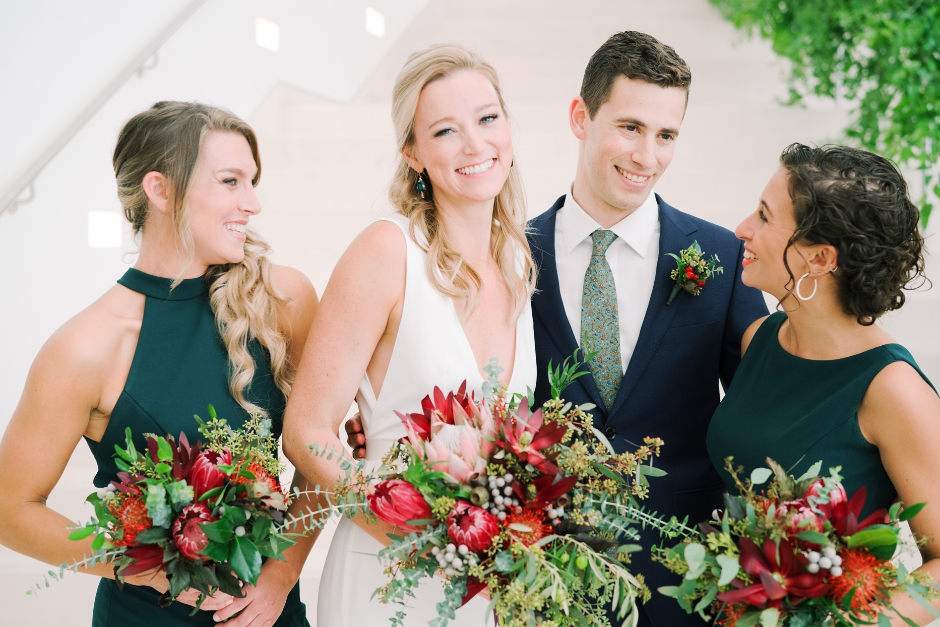 bride and groom with two bridesmaids wearing emerald green dresses