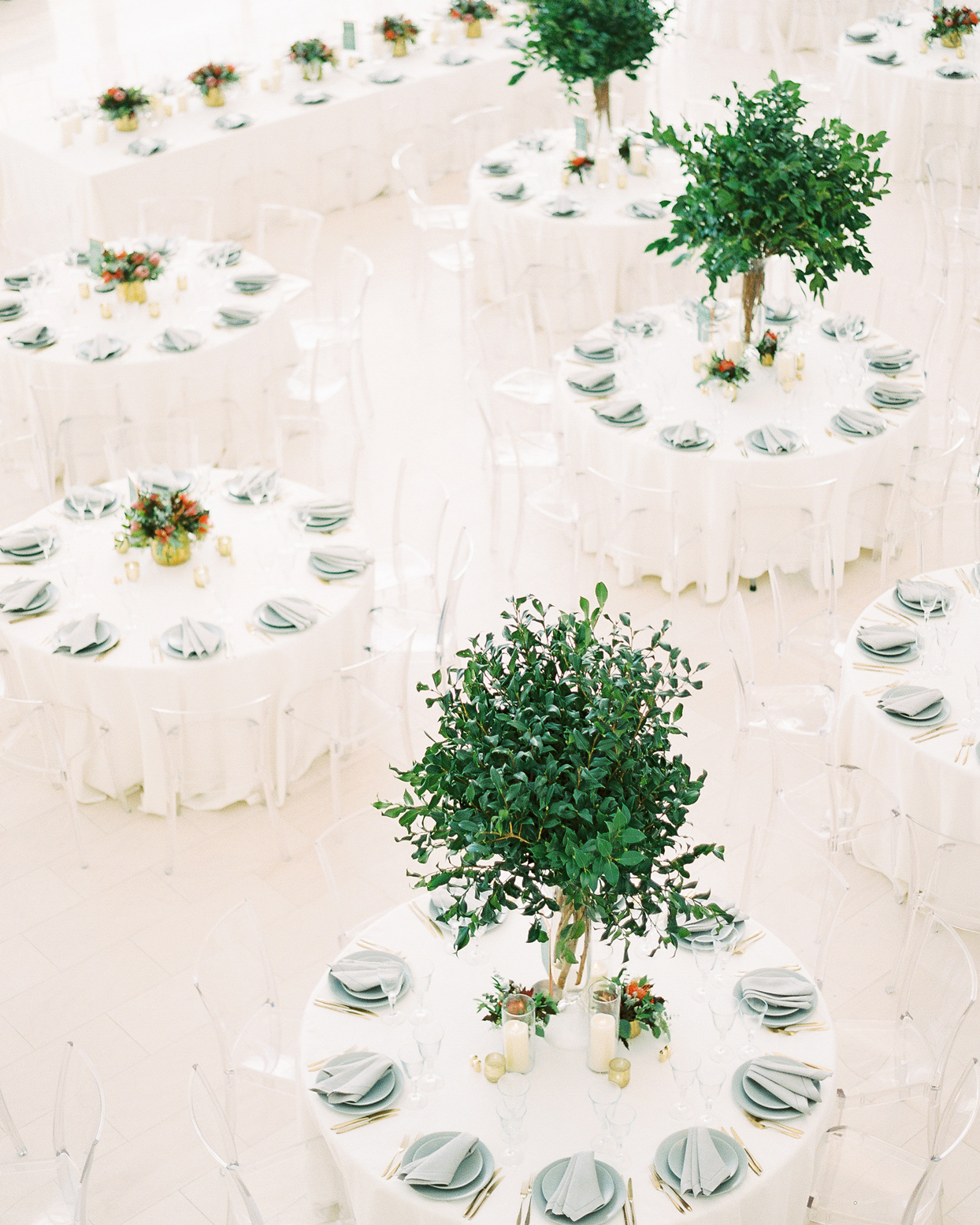 round white linen covered reception tables with clear plastic seating