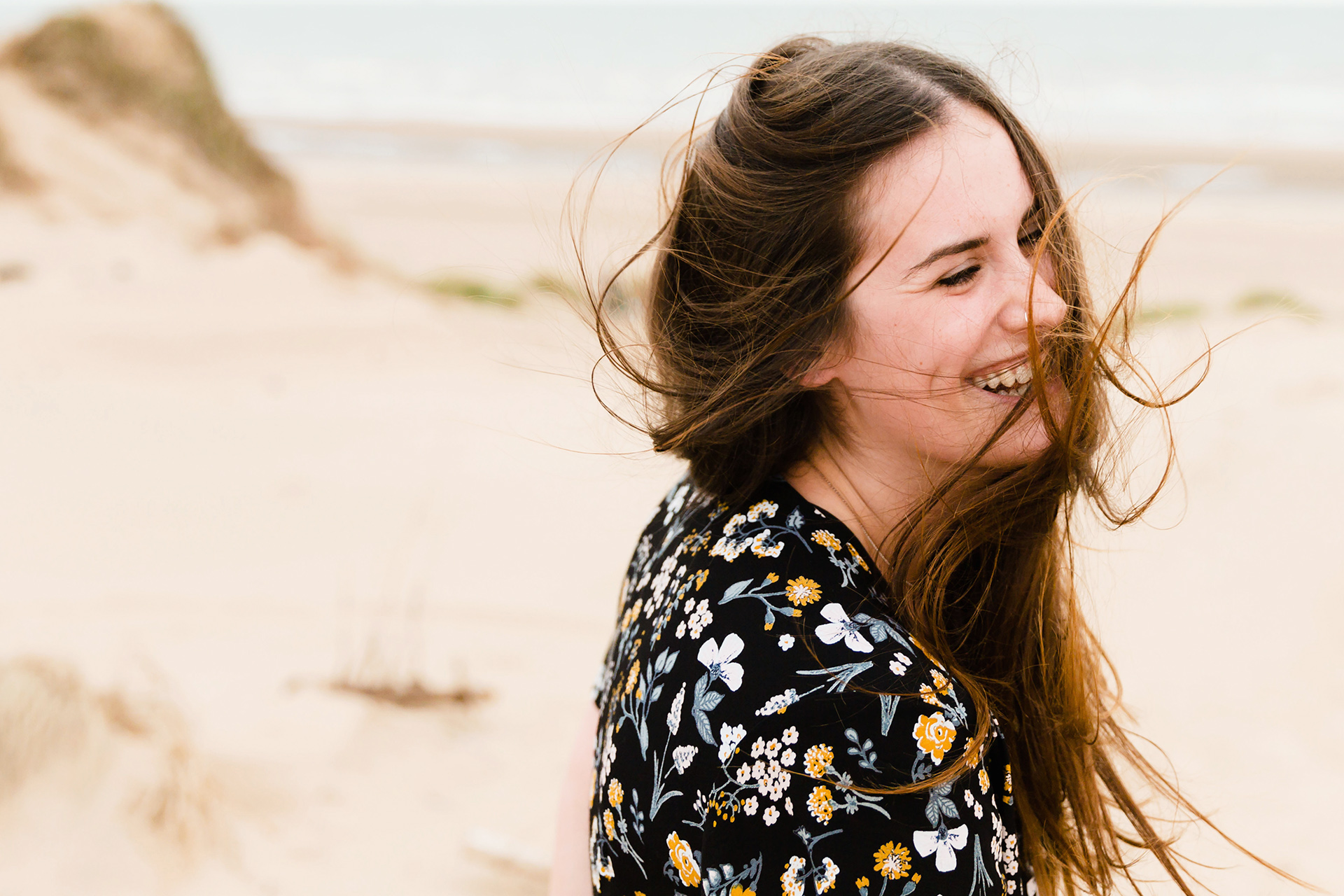 Portrait of laughing woman with blowing hair on the beach
