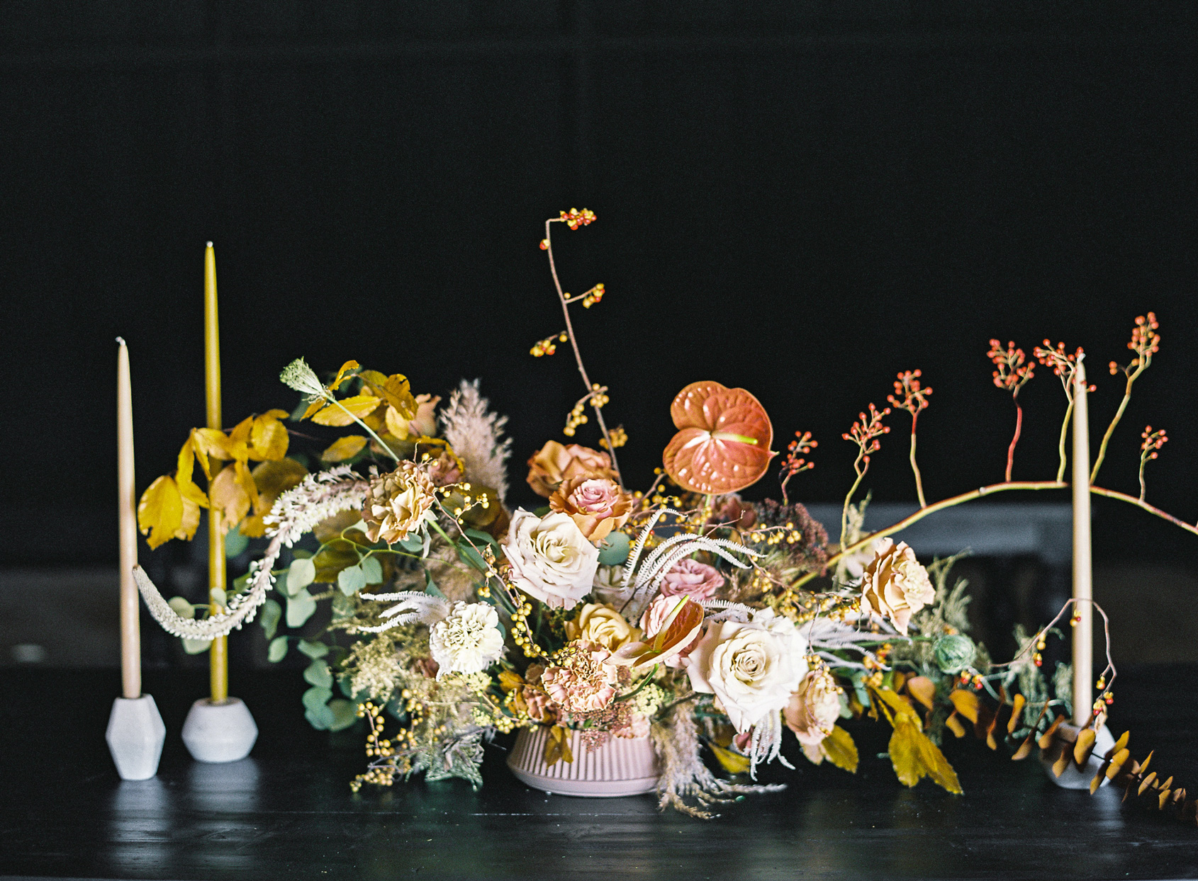 wedding reception centerpiece comprised of wild flowers in blush vase