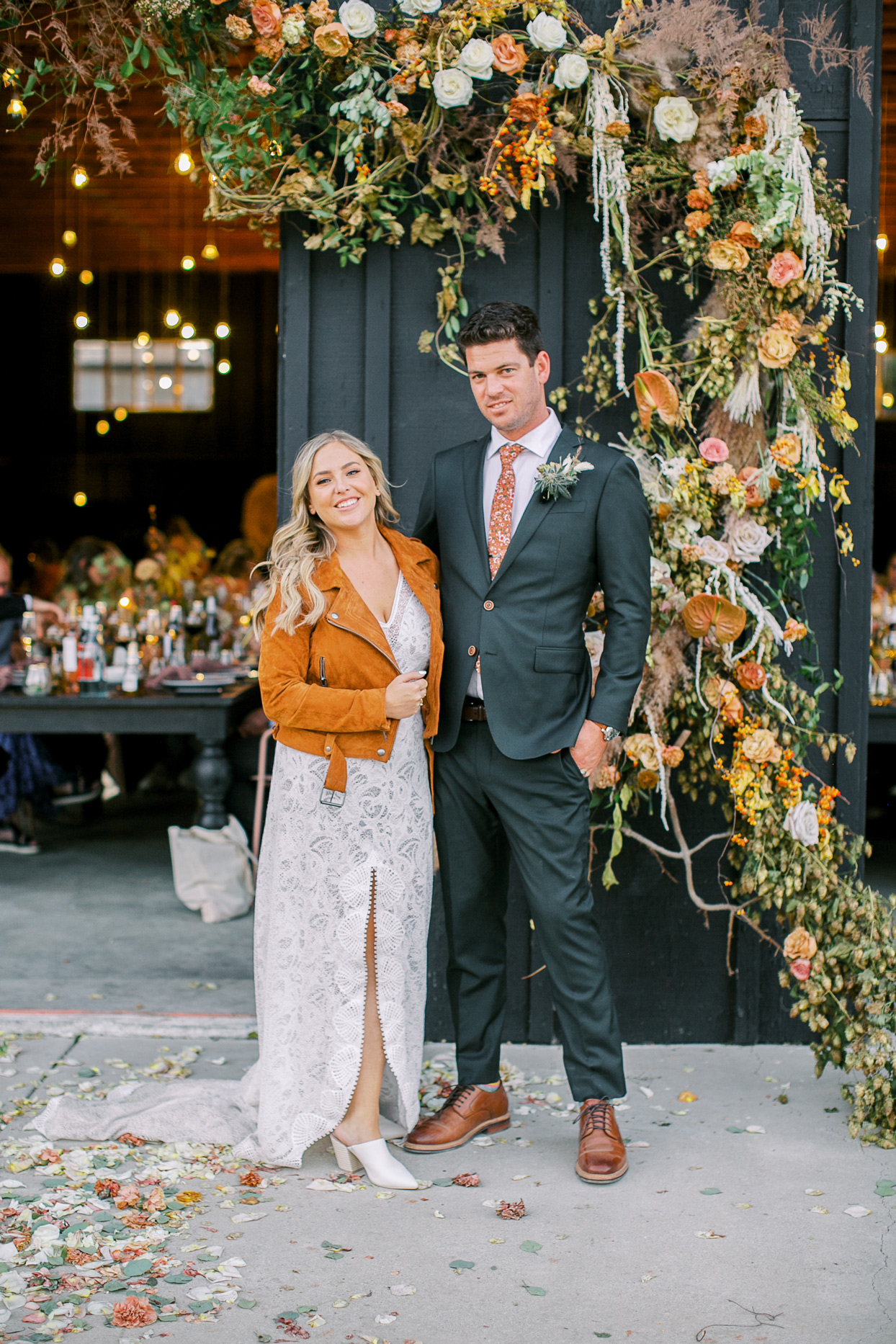 bride and groom posing in front of barn door