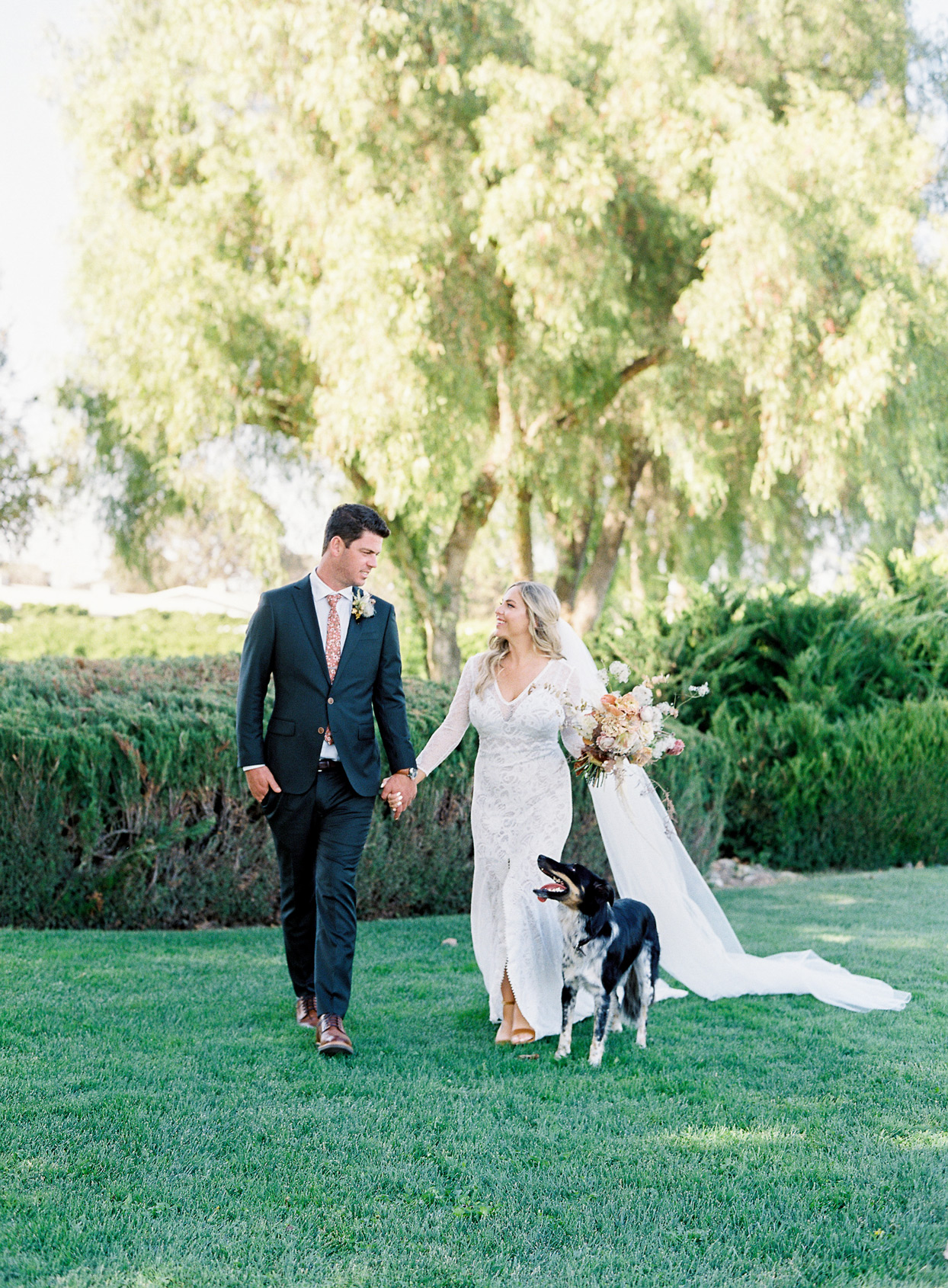 bride and groom walking with dog
