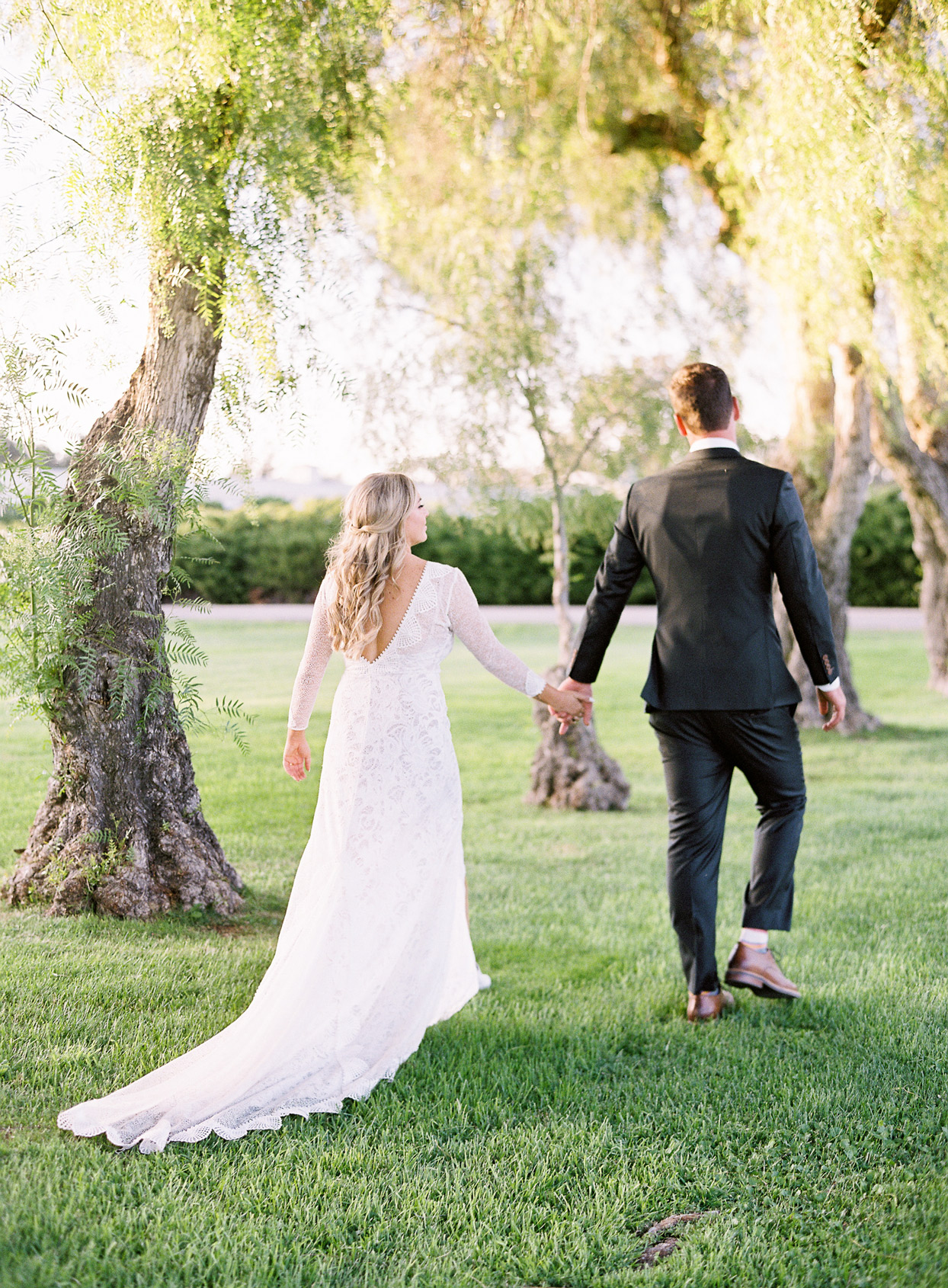 bride and groom holding hands and walking by trees
