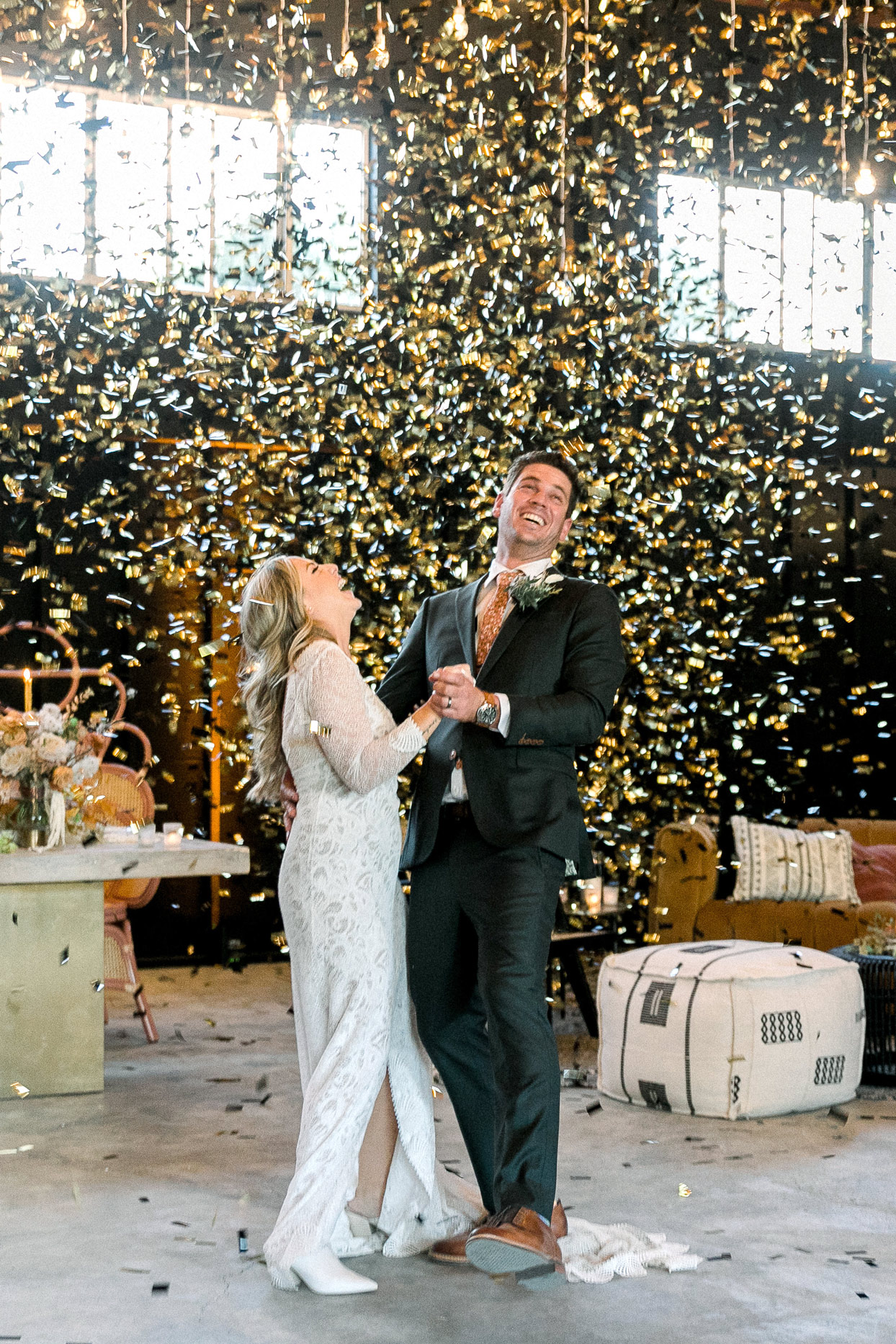 bride and groom sharing first dance beneath gold confetti