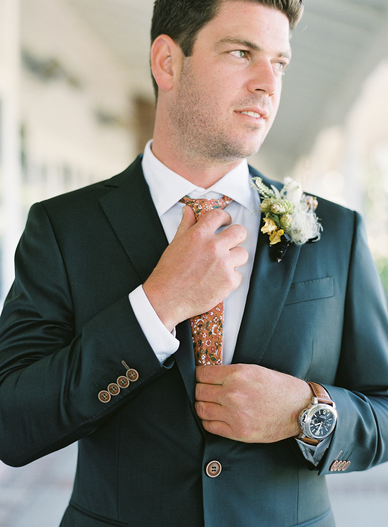groom adjusting floral necktie