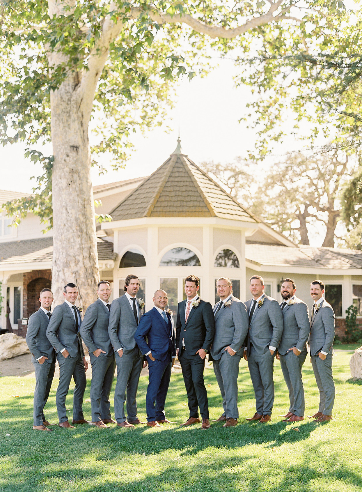 groom and groomsmen posing on lawn