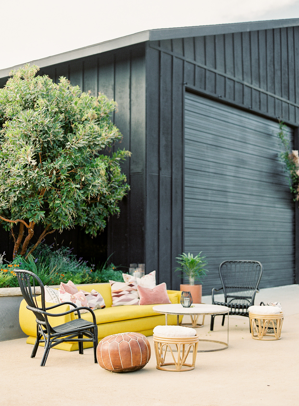 outdoor lounge space with bold colored couches and black wicker chairs
