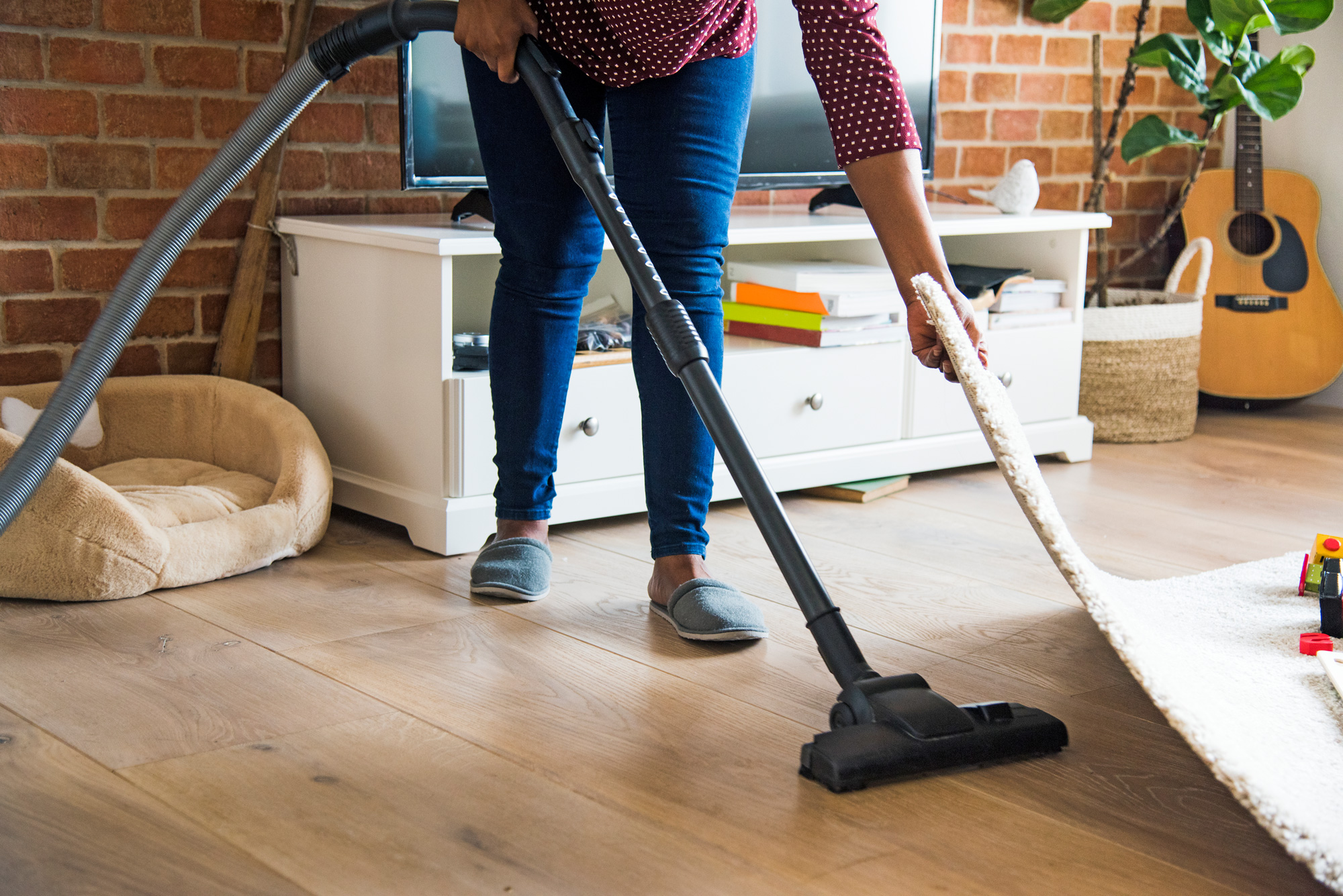 woman vacuuming hardwood under rug