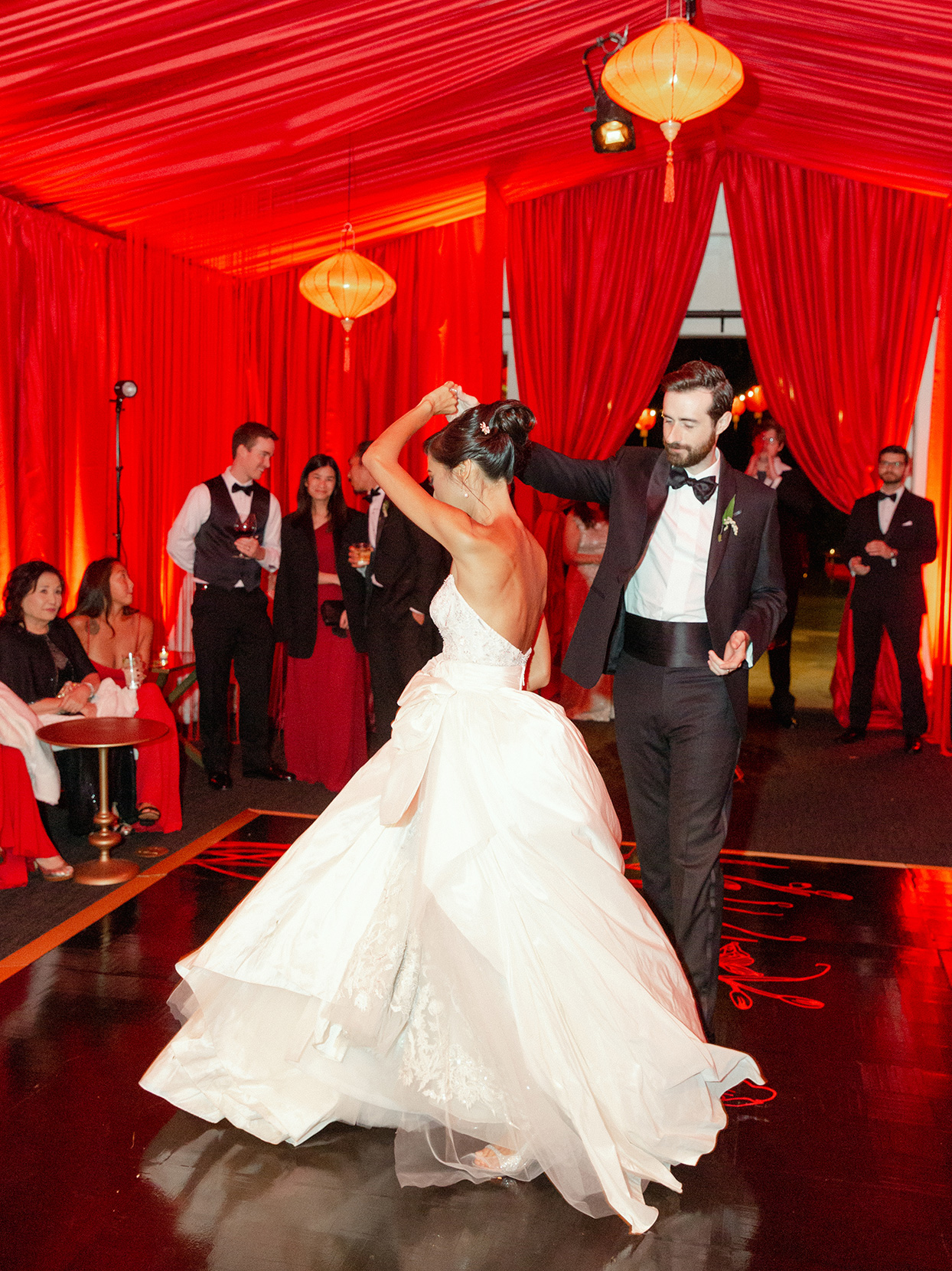 Bride and groom dancing in red-draped room