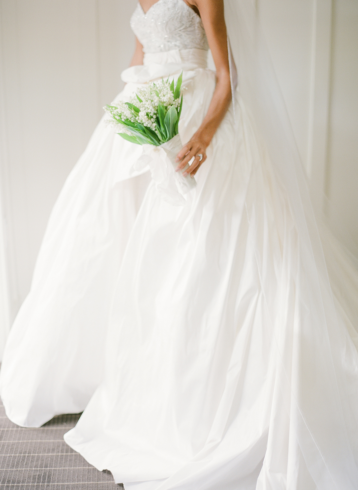 Bride in strapless sheath gown paired with a silk taffeta ball gown overskirt with a slit and an asymmetrical bow
