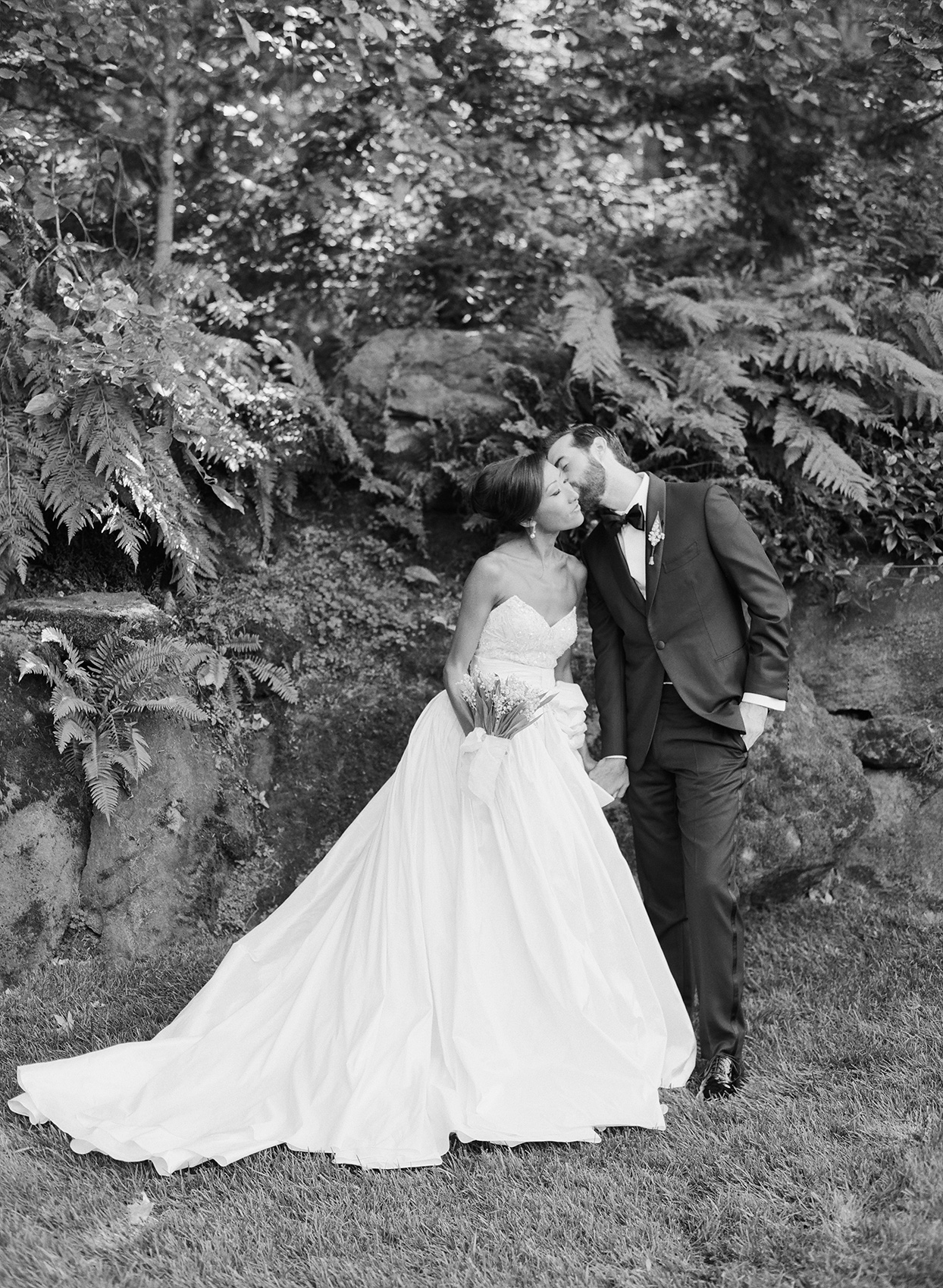 Bride and groom in front of foliage