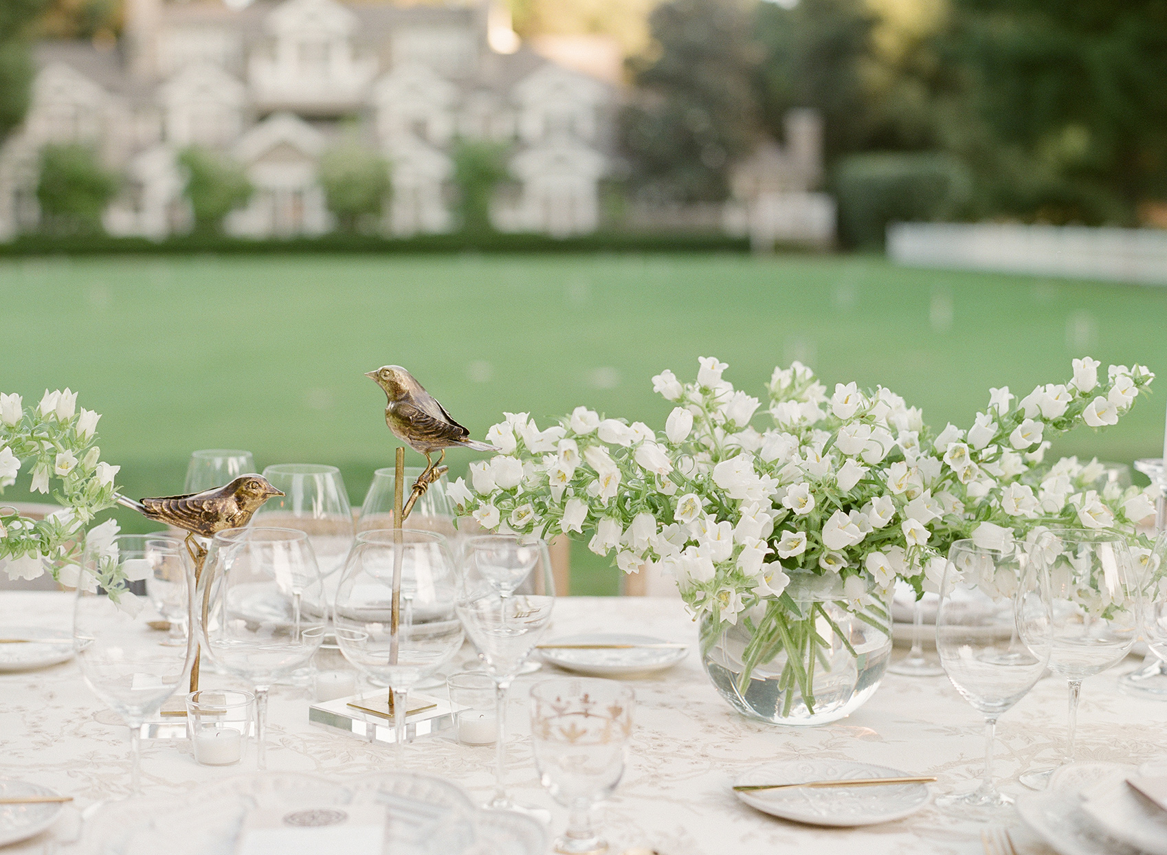 Wedding reception tables with low all-white canterbury bell centerpieces in clear bowl vases
