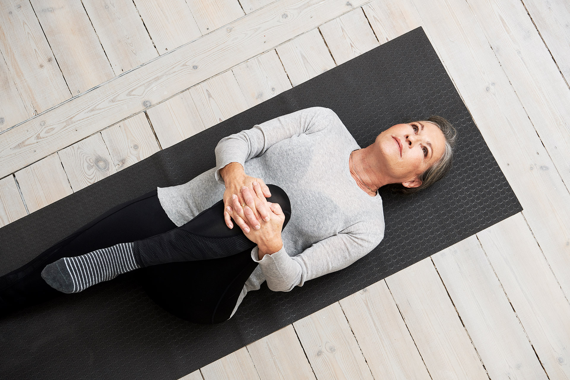 healthy older woman stretching on yoga mat