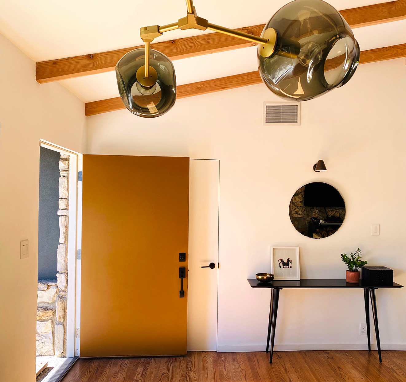 open mustard colored front door into modern house