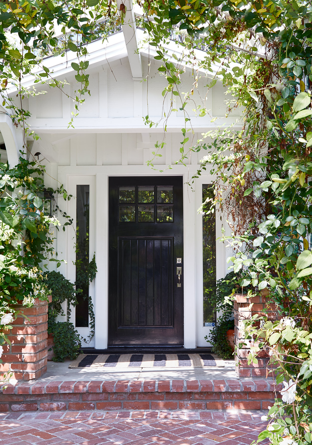 black front door on white house with brick entry way