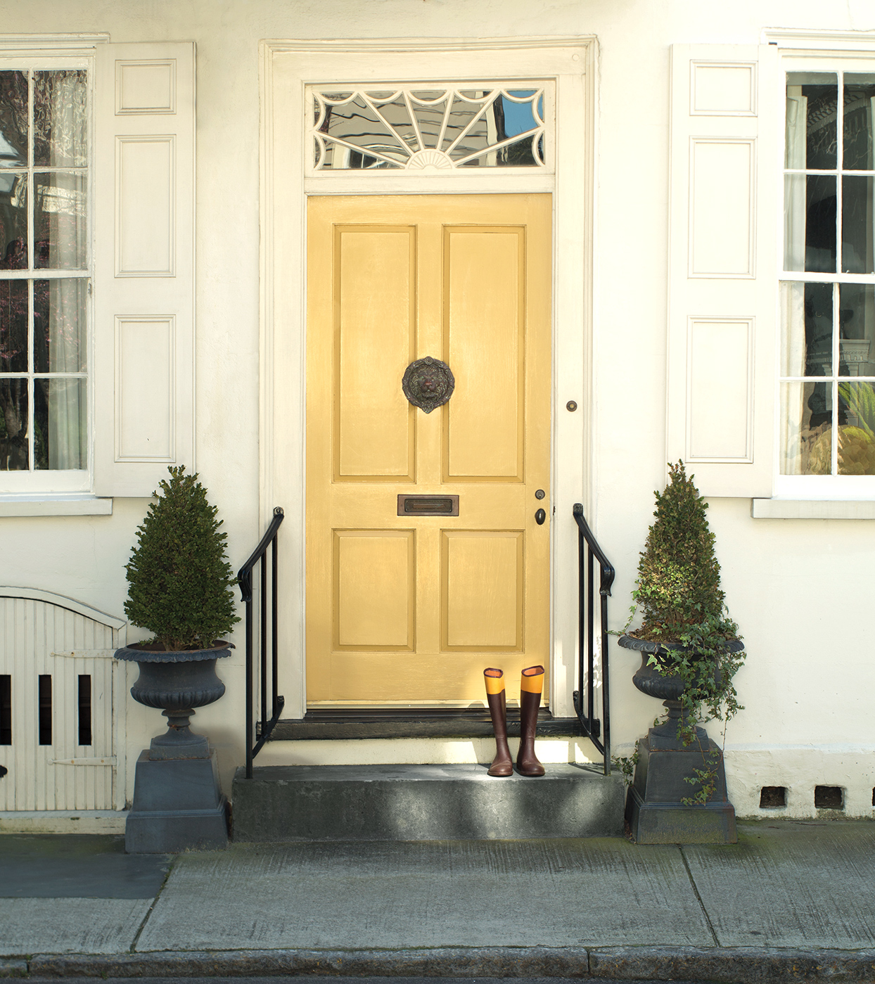 pale yellow front door on town house with tree decorations