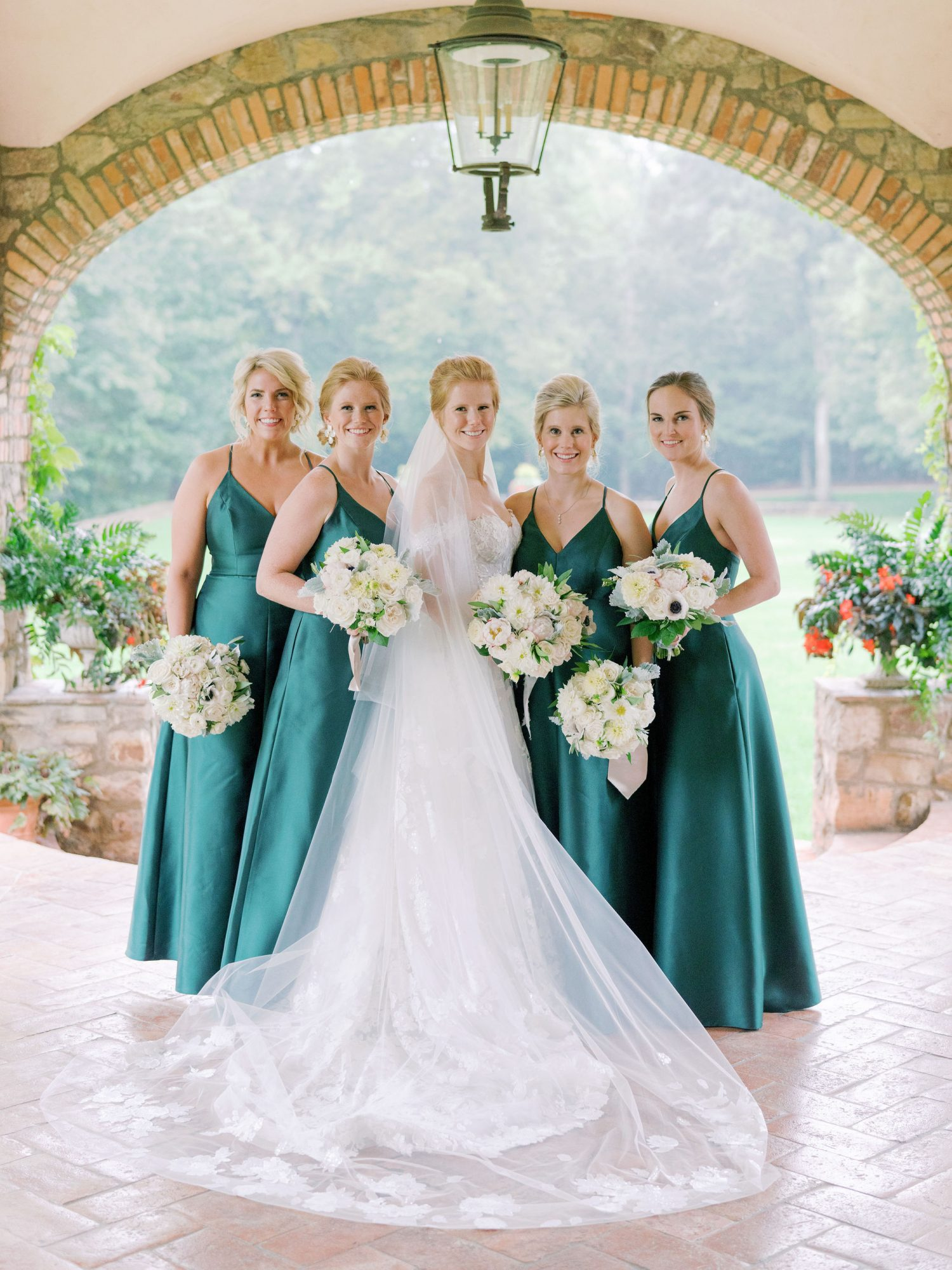 bride with 4 bridesmaids wearing emerald green dresses