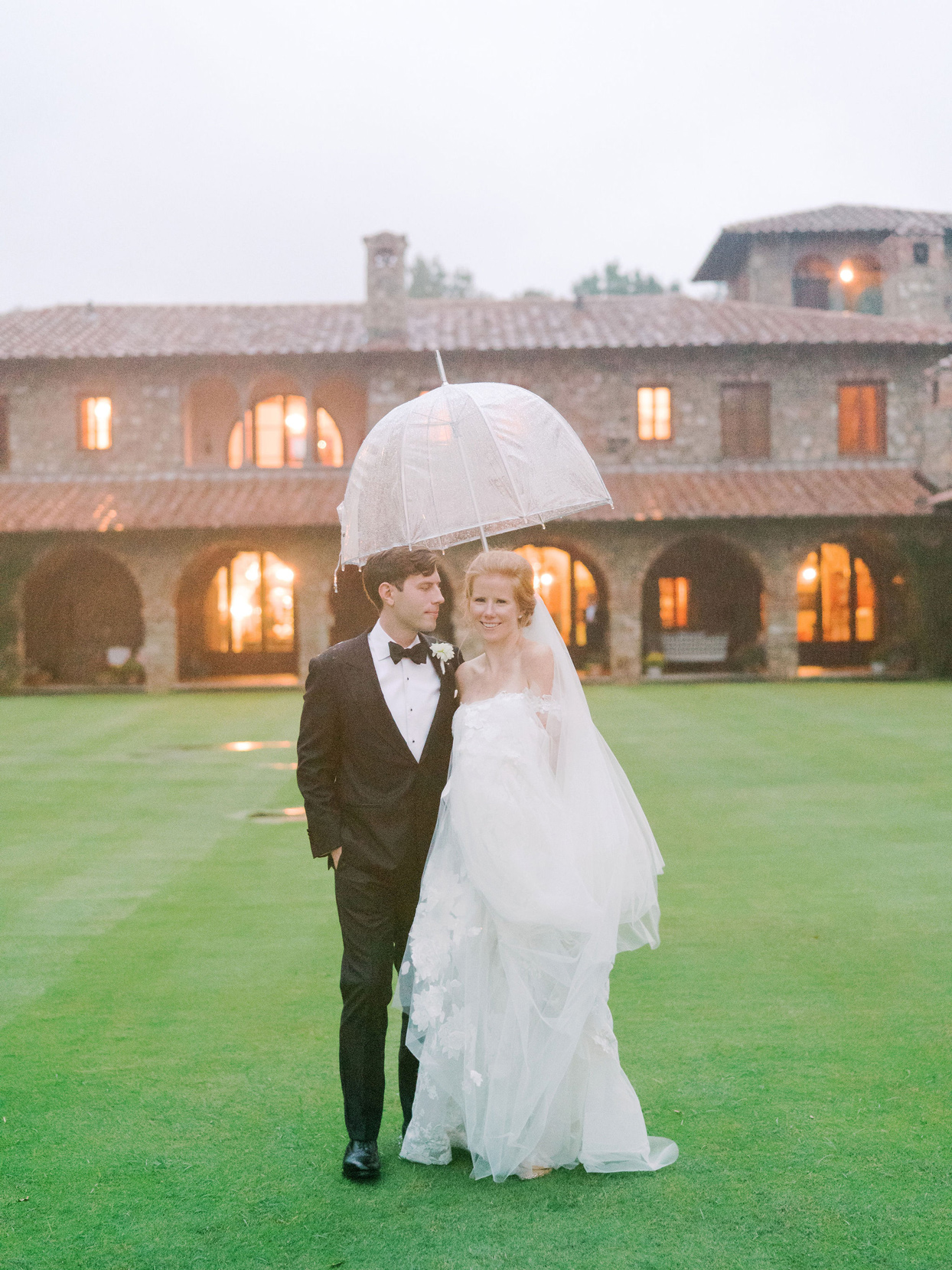 bride and groom outside wedding venue under umbrella