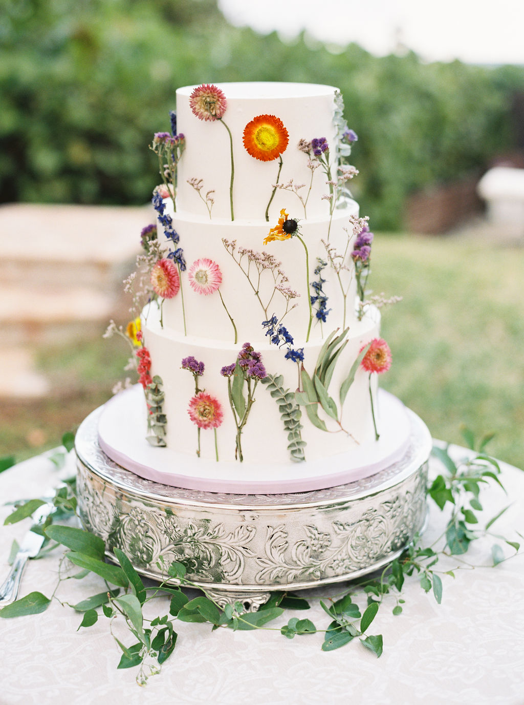simple white wedding cake with pressed flower decorations