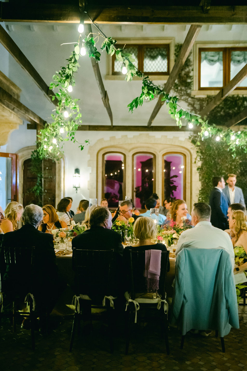 guests eating wedding dinner under the lights on the patio