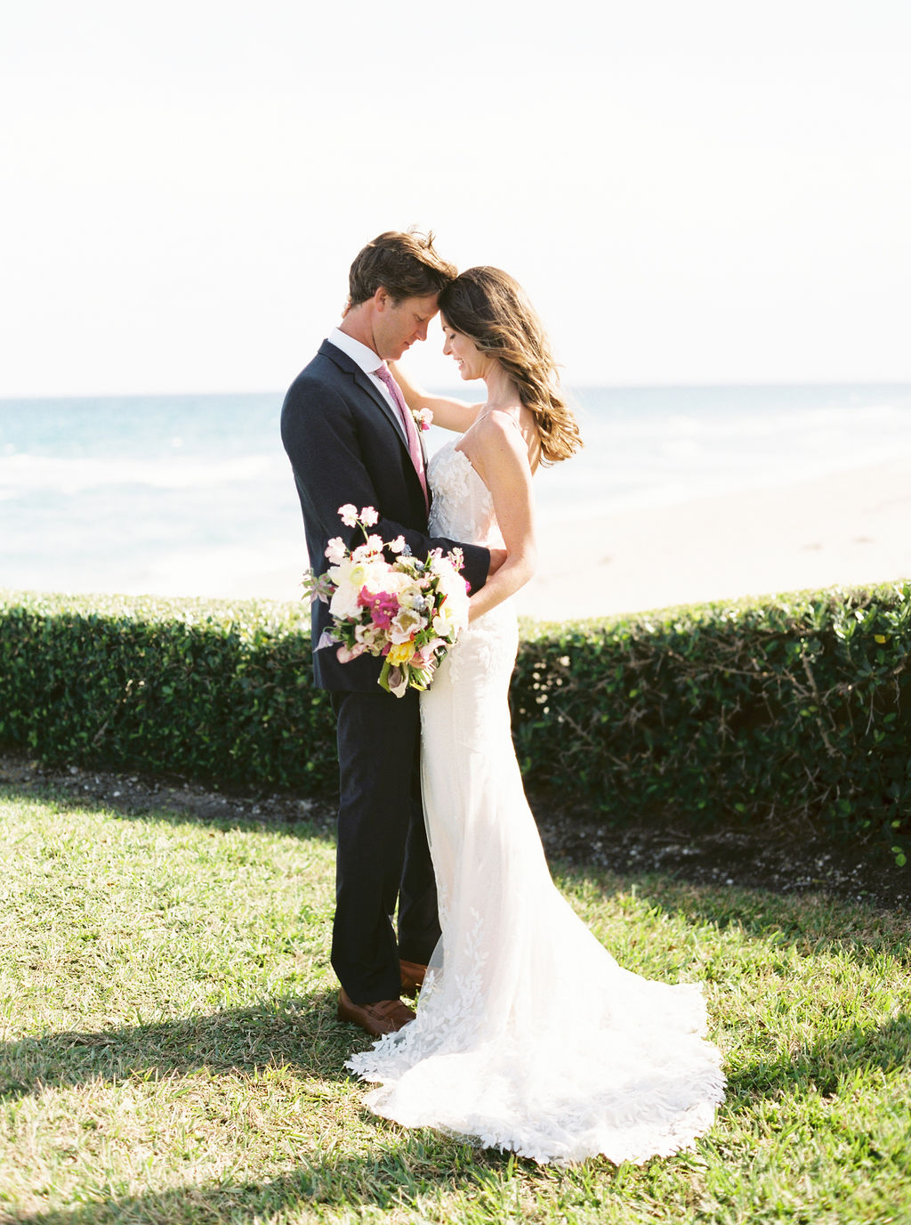 couple embracing during first look with beach view