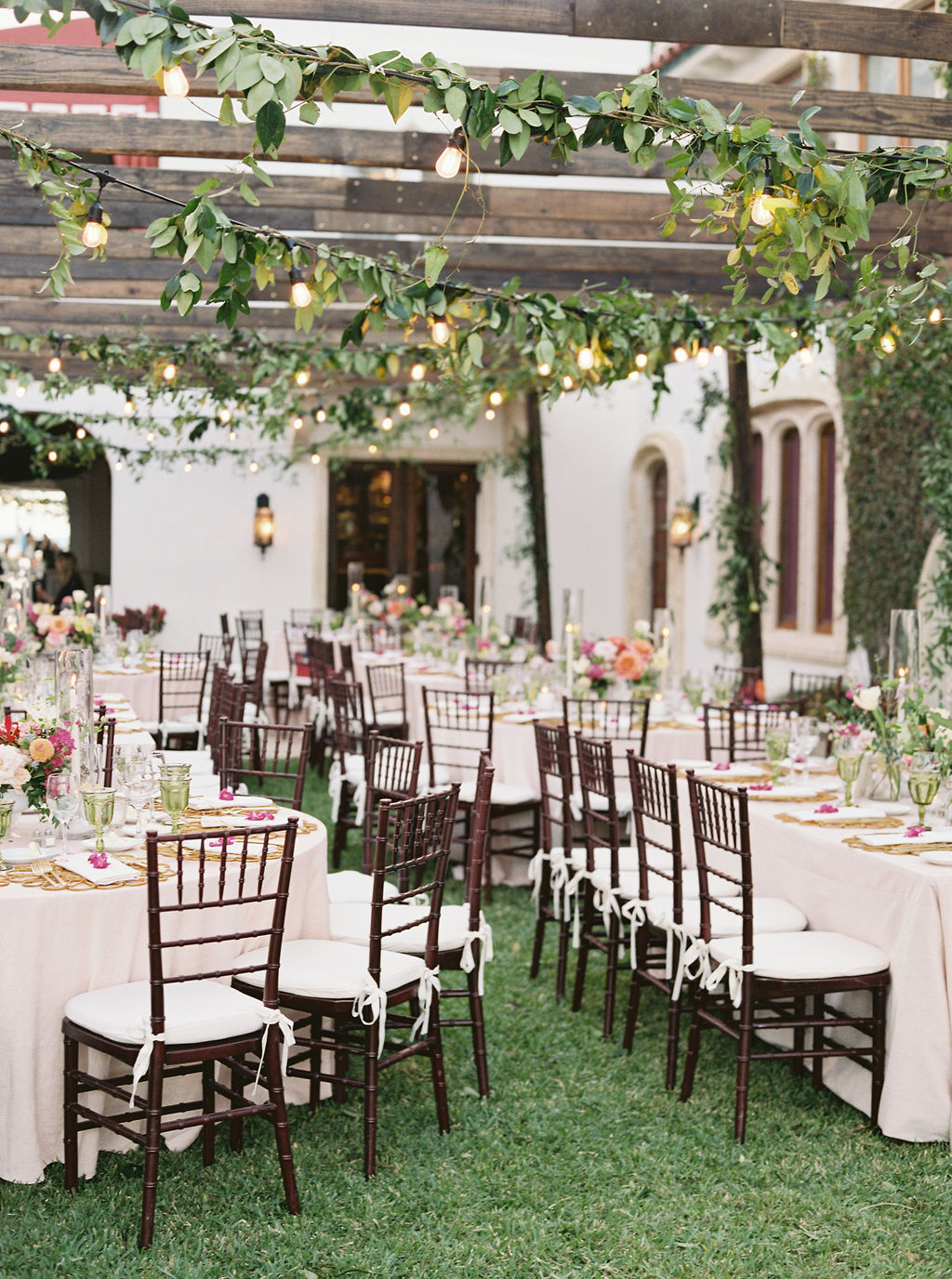 backyard reception with elegant white tables with floral accents