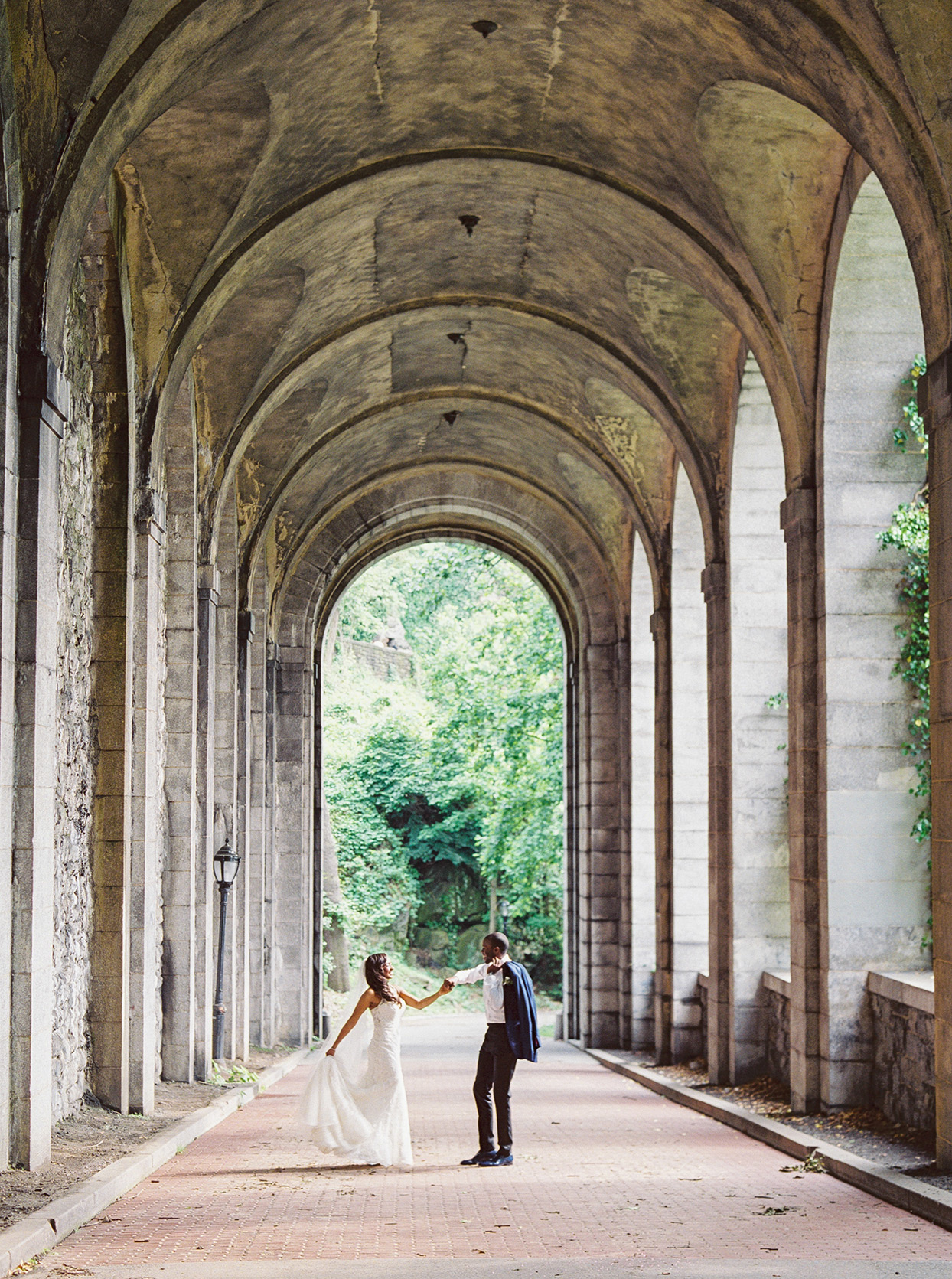 wedding couple dancing under stone arching columns at park