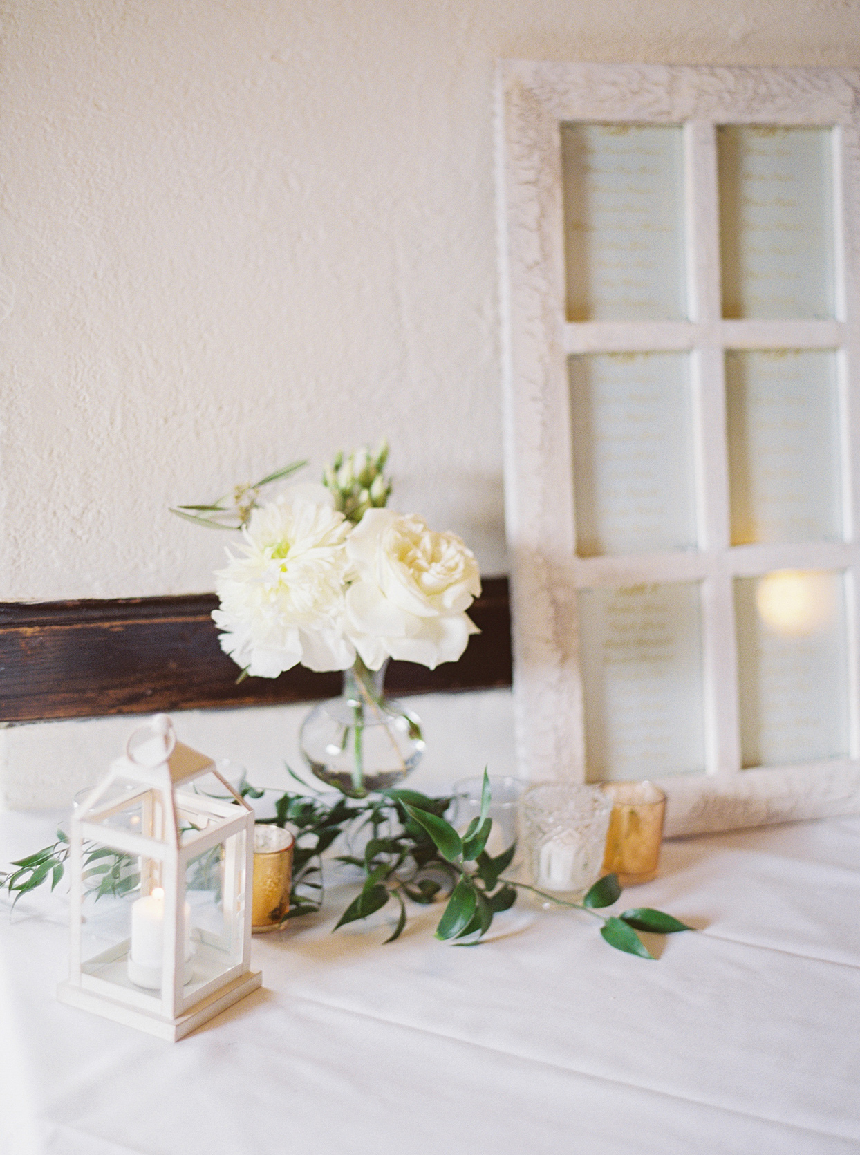 wedding seating chart in ornate frame on white table