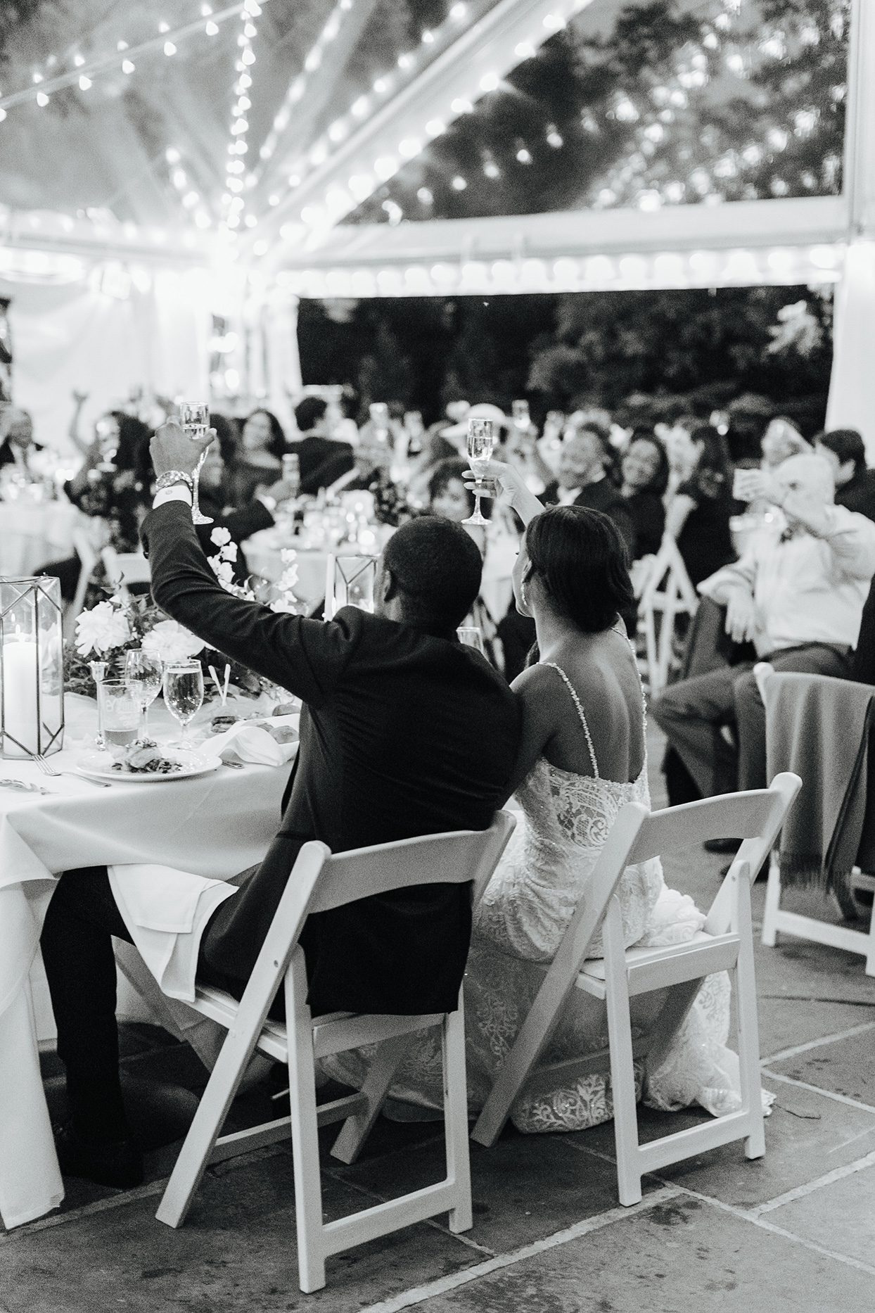 wedding couple sitting at sweetheart table toasting champagne