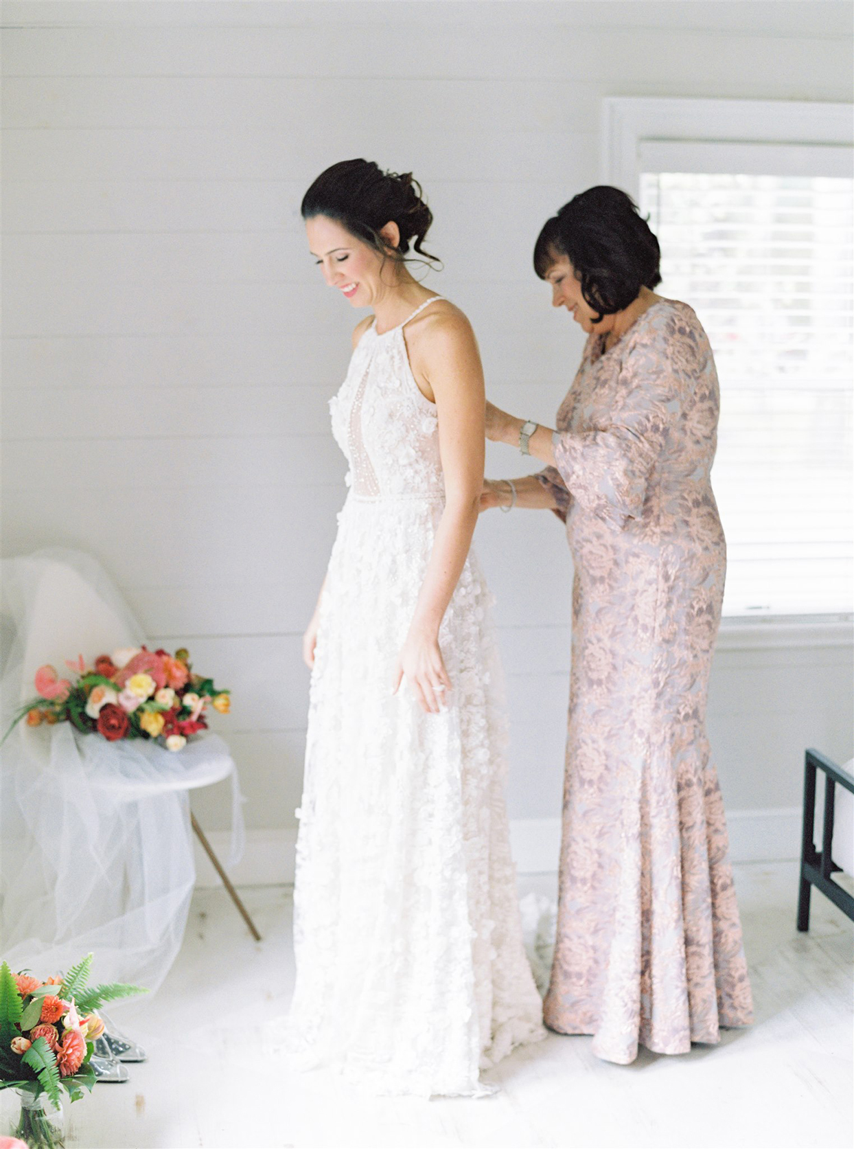 bride getting ready with help of mother in pastel pink dress