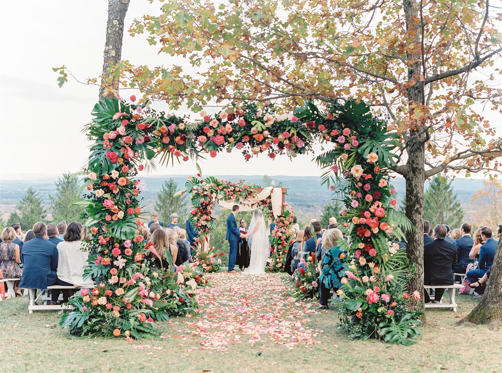couple holding hands during outdoor wedding ceremony with guests seated on benches